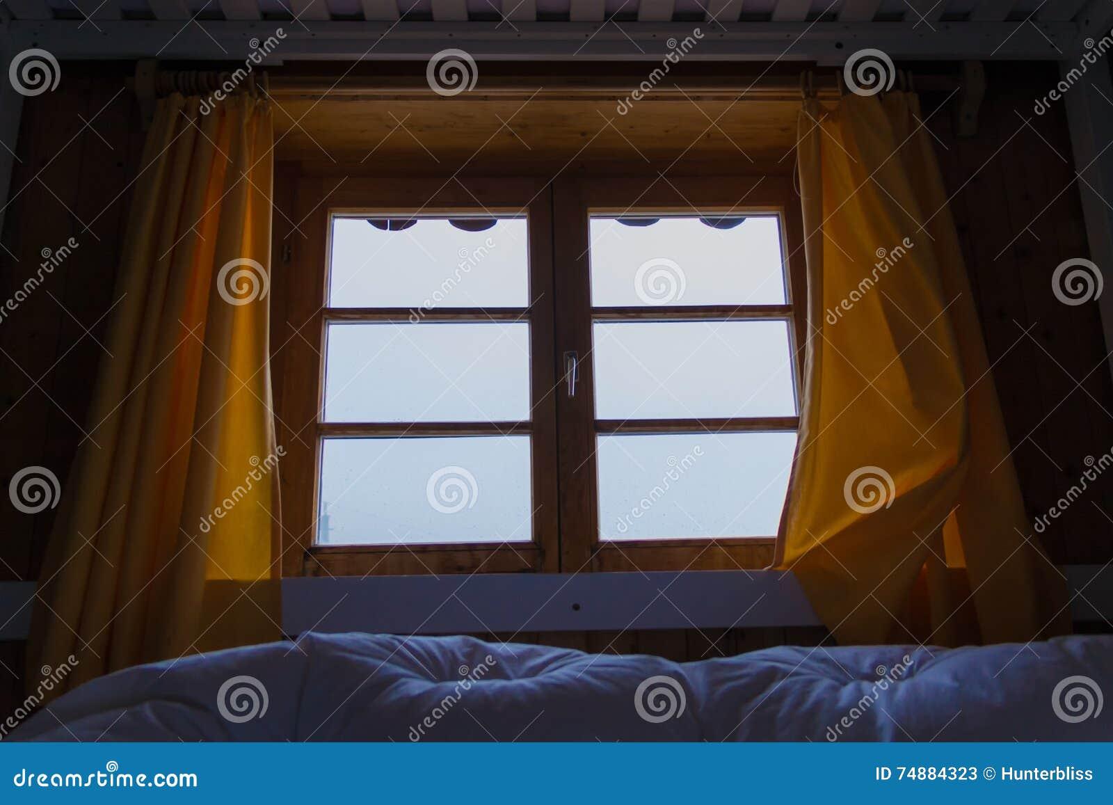 Olhando a manhã nevoenta do inverno das montanhas das cortinas de janela da cama