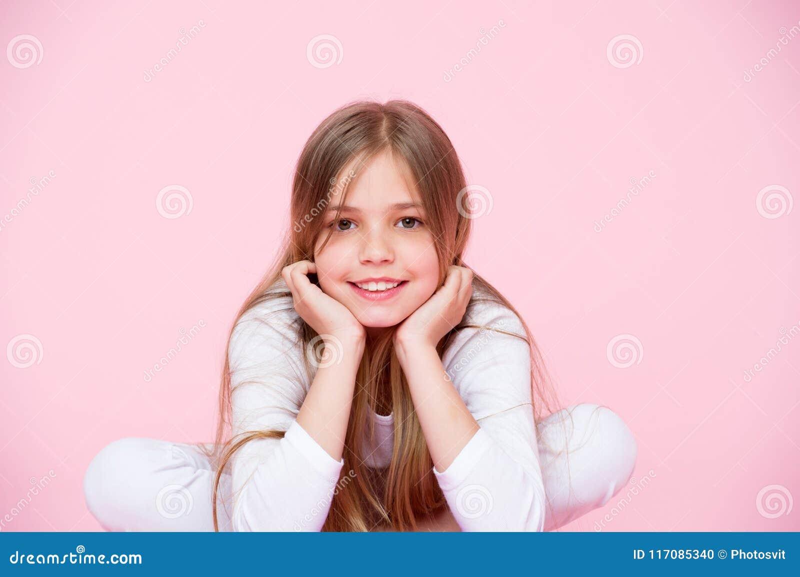 Olhar da beleza e cuidados capilares, cor pastel punchy Fundo do rosa do sorriso da menina Criança feliz com cara bonito Criança