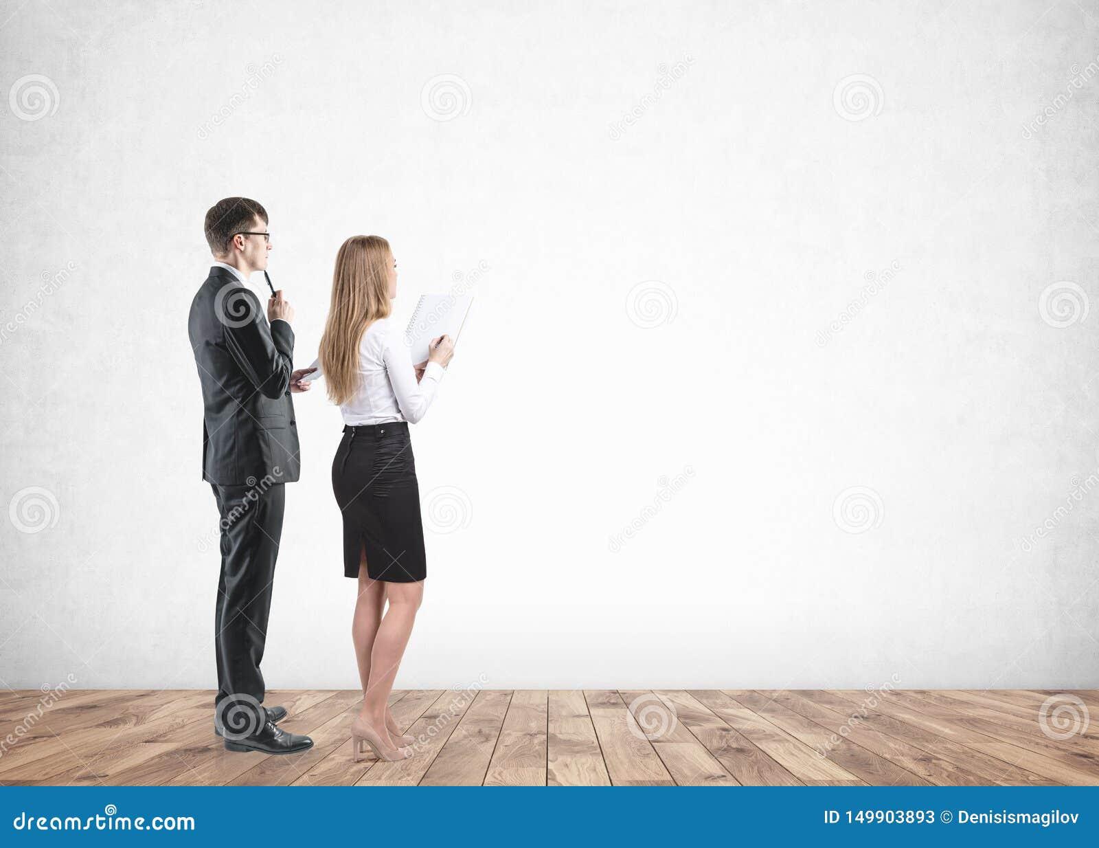 Olhar do homem de negócios e da mulher de negócios na parede vazia