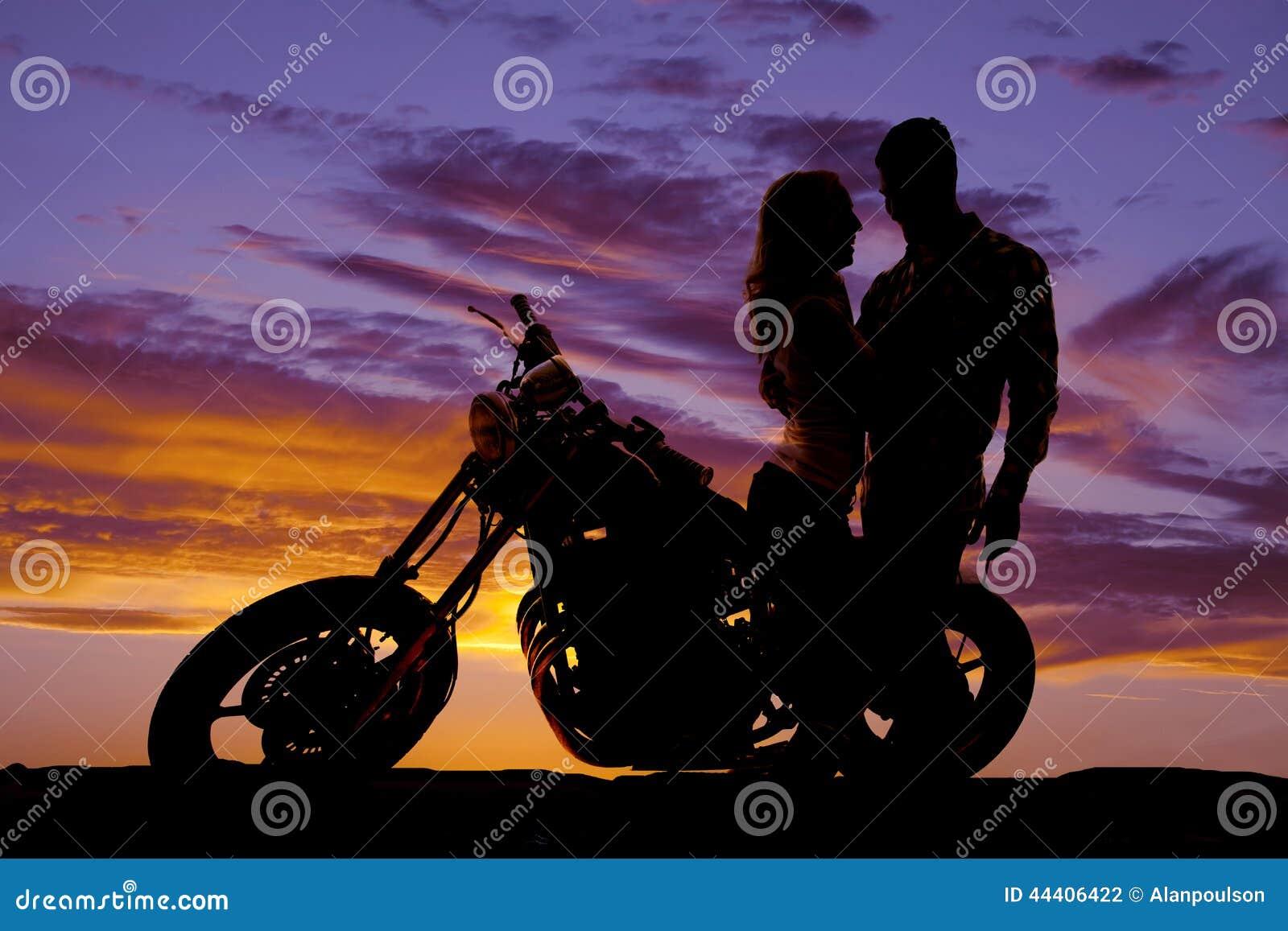 Olhar dos pares da silhueta em se na motocicleta