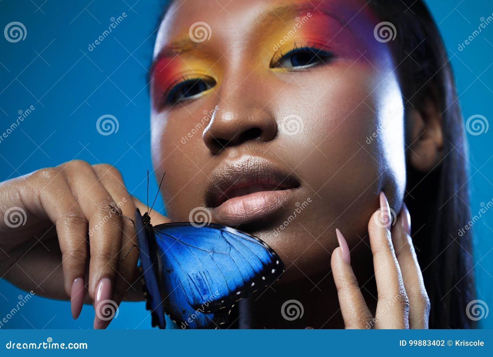 Olhar exótico modelo preto novo e bonito com a borboleta azul brilhante