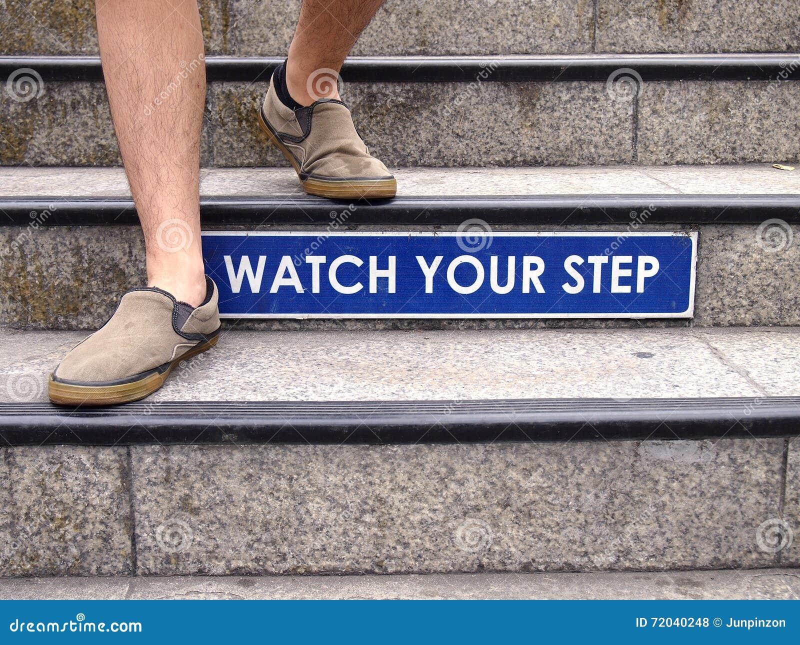 Olhe seu sinal da etapa em uma escadaria e um par de pés