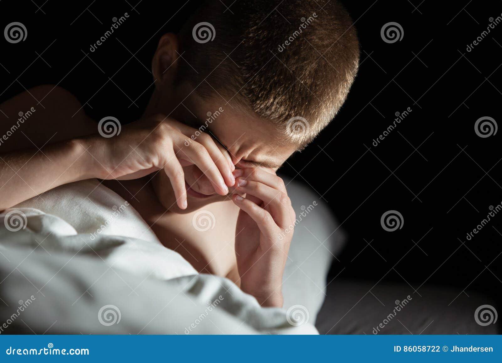 Olhos da fricção do menino ao levantar-se da cama