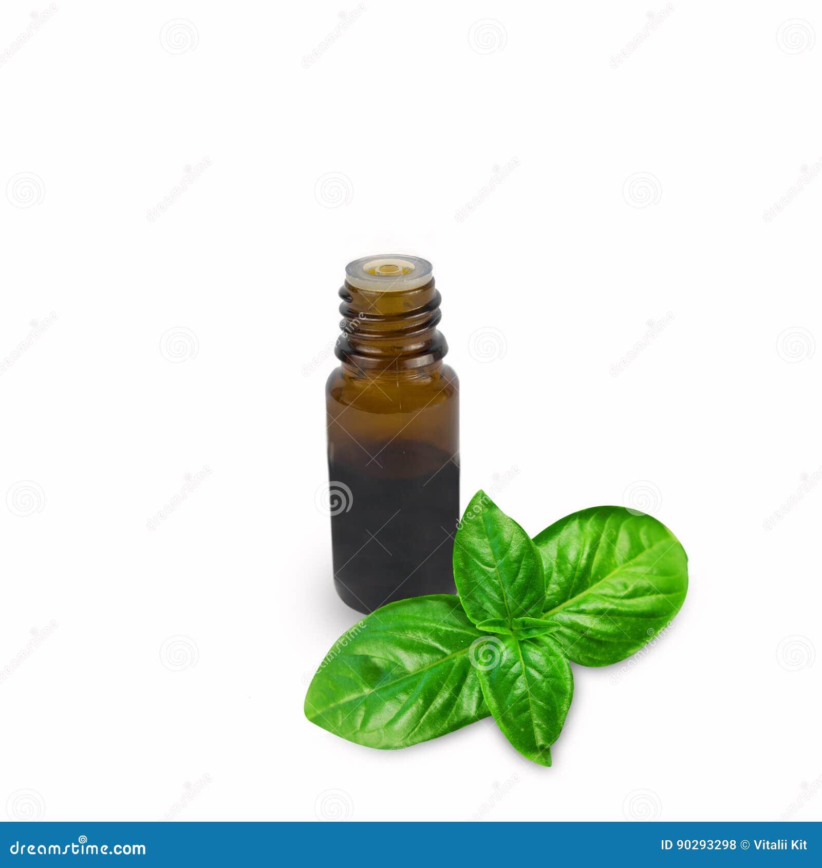 Oli essenziali del basilico in bottiglia isolata su un fondo bianco