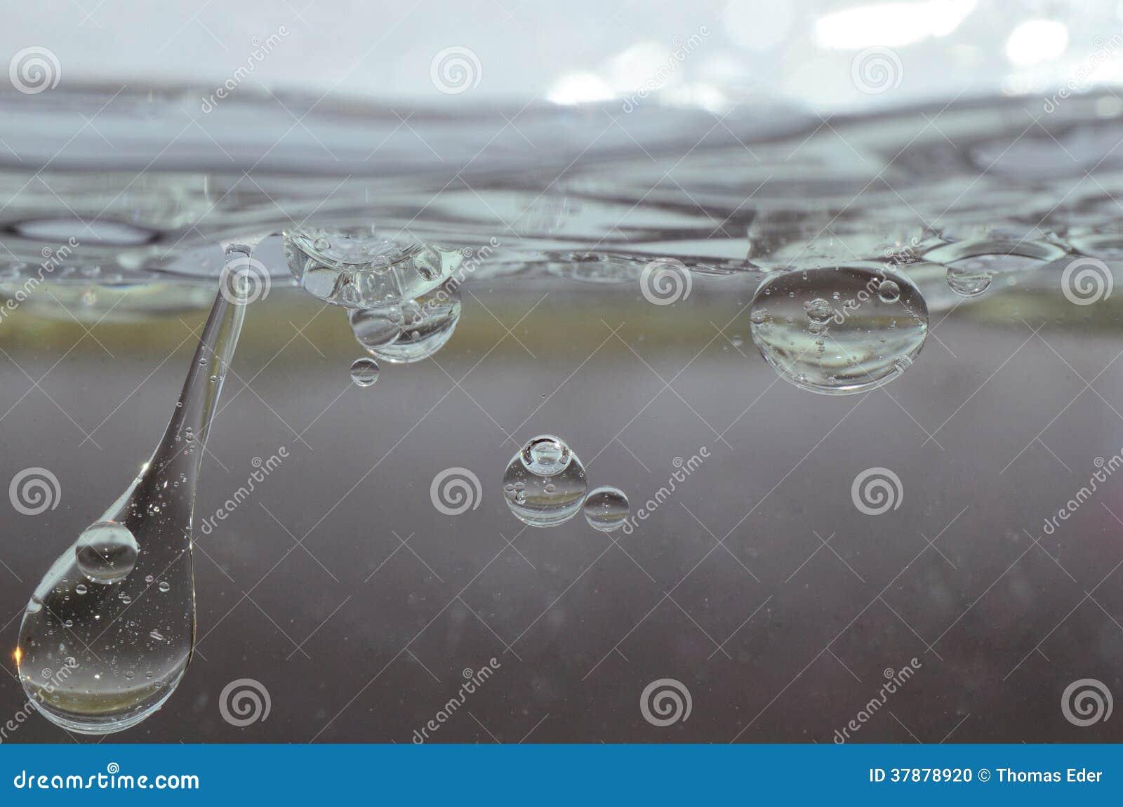 Oliedruppeltjes in het transparante water