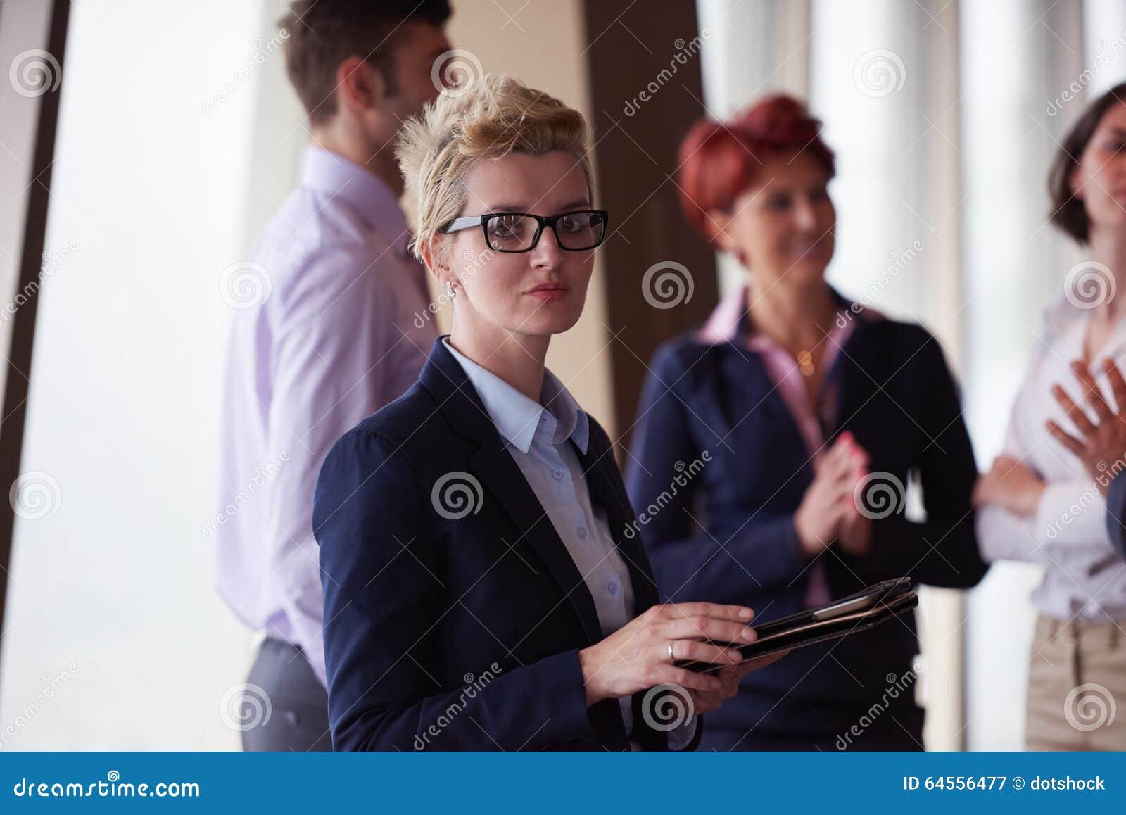 Olik grupp för affärsfolk med den främsta blonda kvinnan