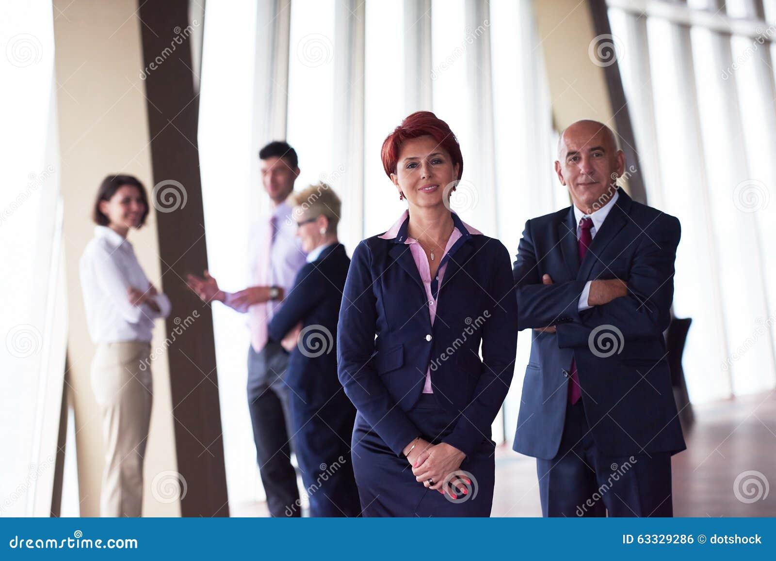 Olik grupp för affärsfolk med redhairkvinnan framme