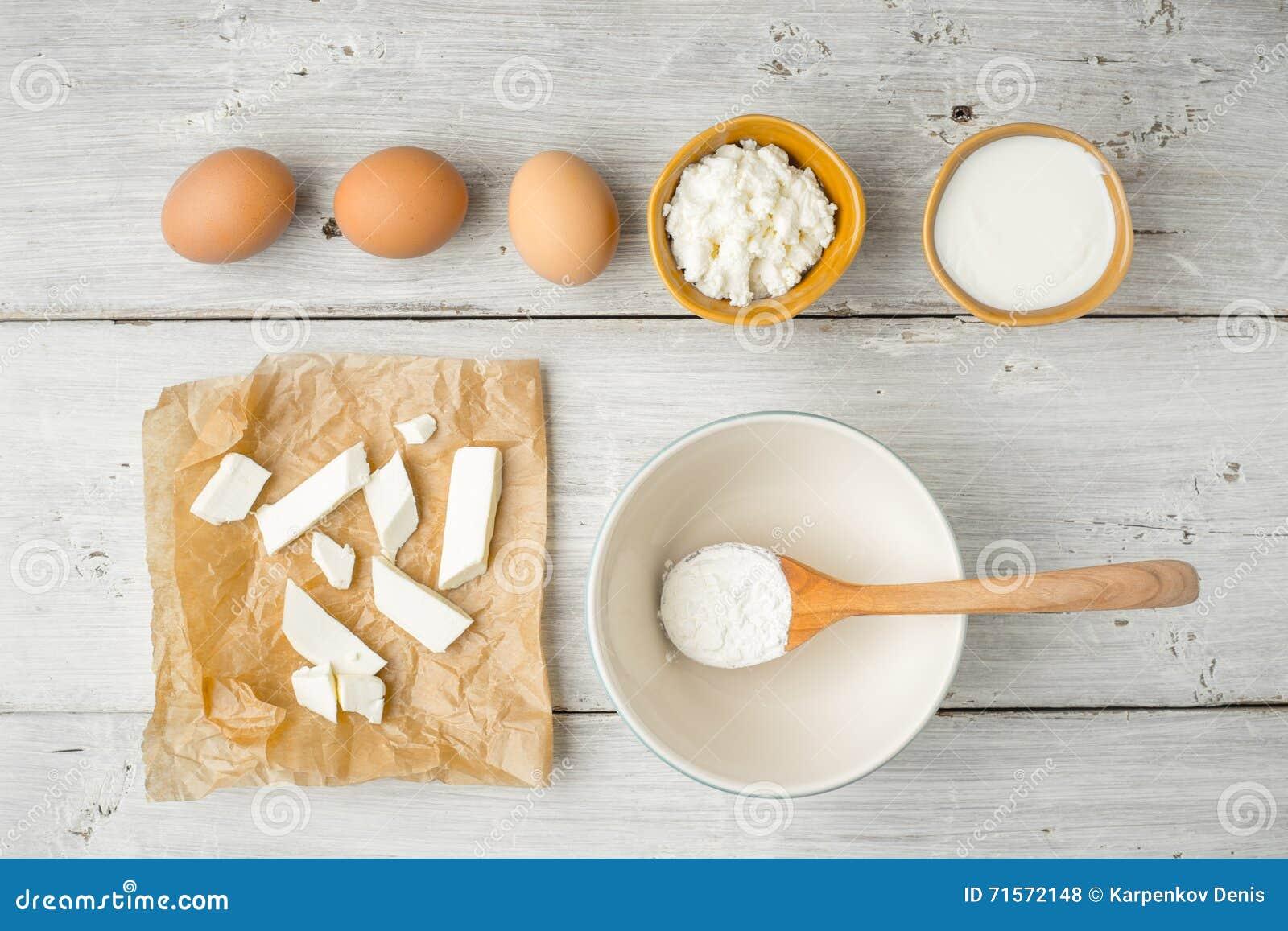 Olik ny ost med yoghurt och ägg på den vita träbästa sikten för tabell