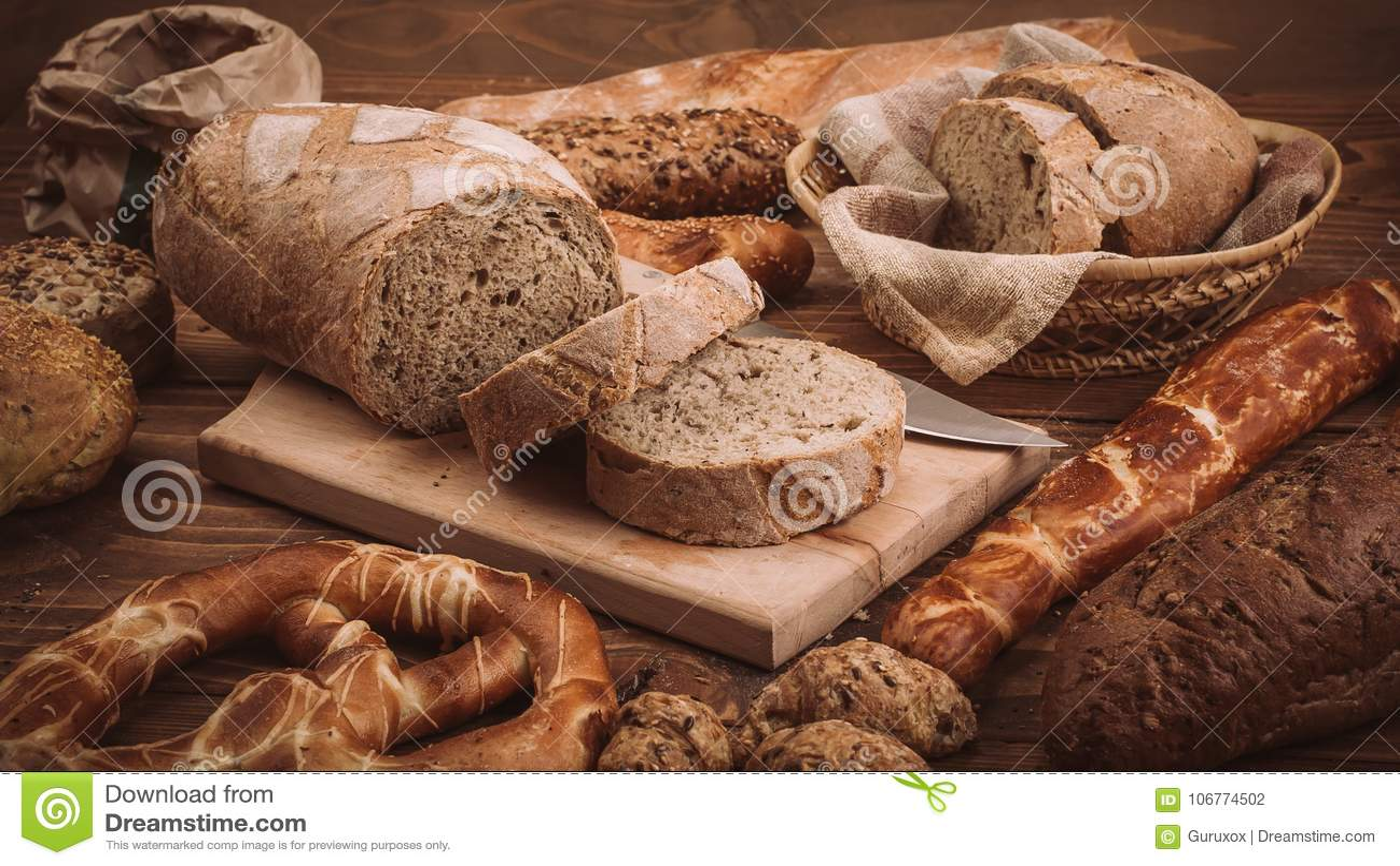 Olika bakade bröd och rullar på den lantliga trätabellen