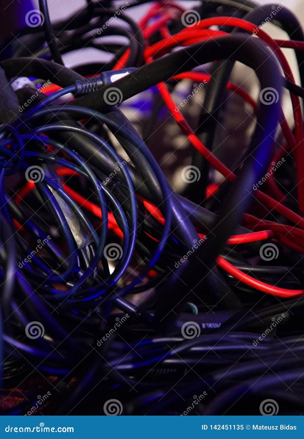 Olika färger av tilltrasslade kablar i oordning