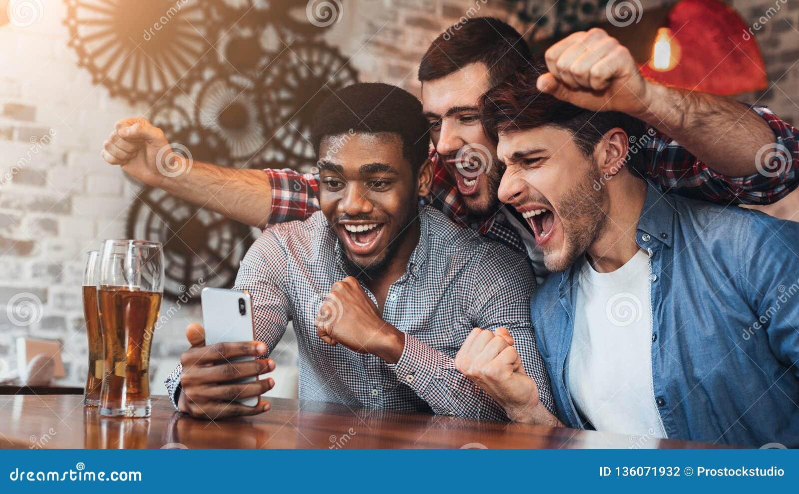 Olika fotbollsfan som håller ögonen på fotboll på smartphoner i bar