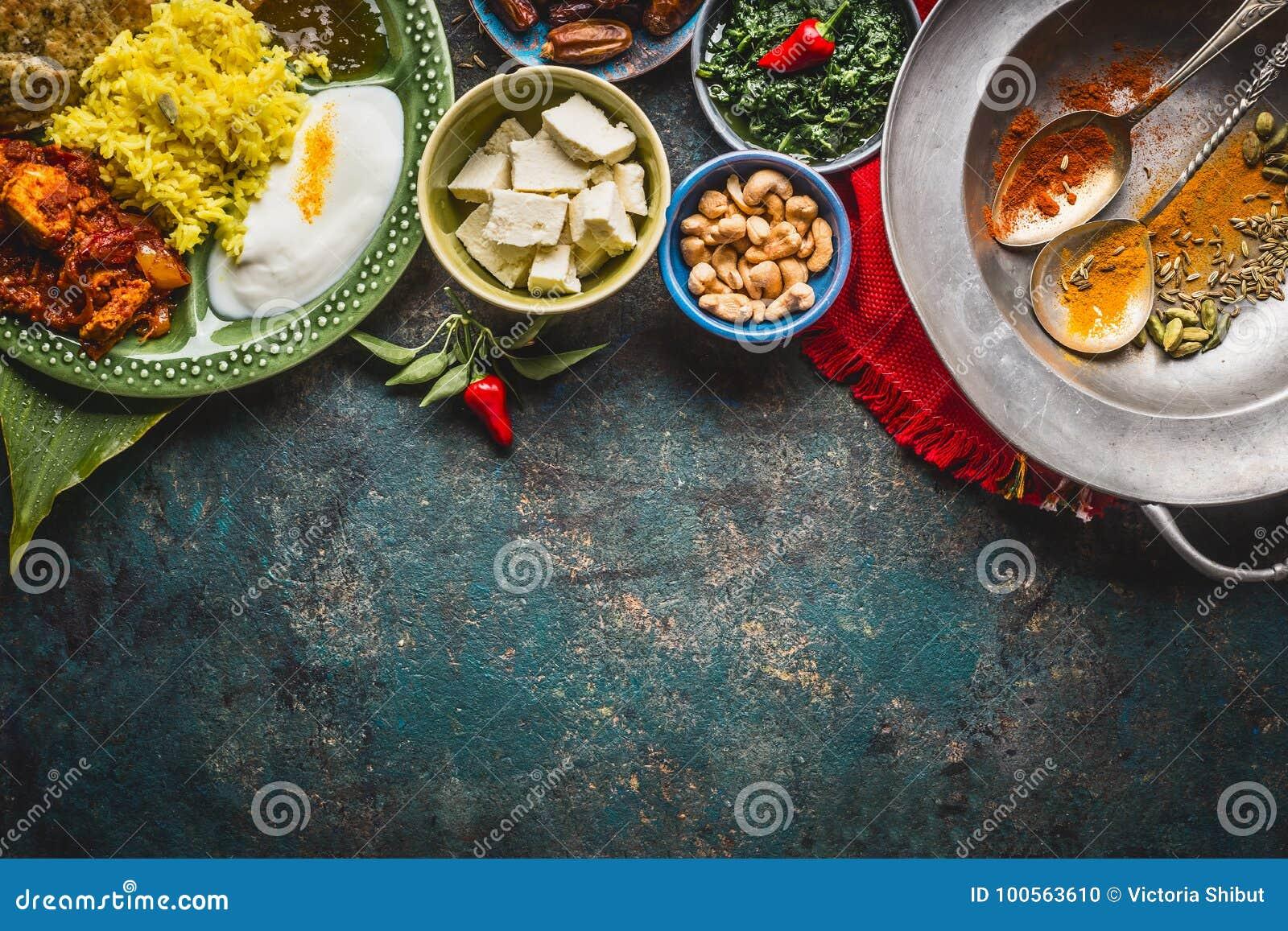 Olika indiska matskålar med curry, yoghurt, ris, bröd, höna, chutney, paneerost och kryddor på mörk lantlig bakgrund, till