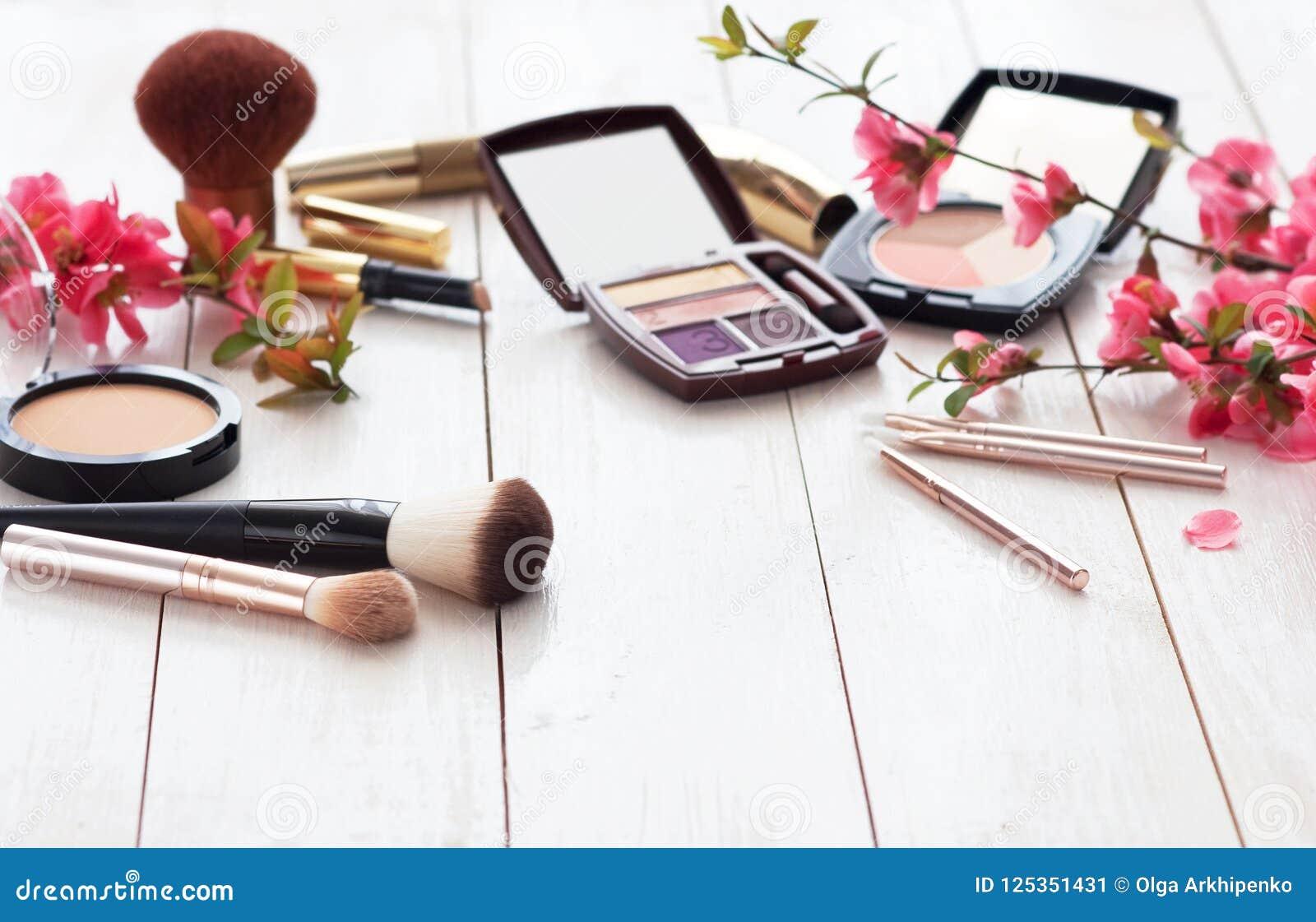 Olika kosmetiska produkter för smink med rosa blommor på en vit träbakgrund med kopieringsutrymme