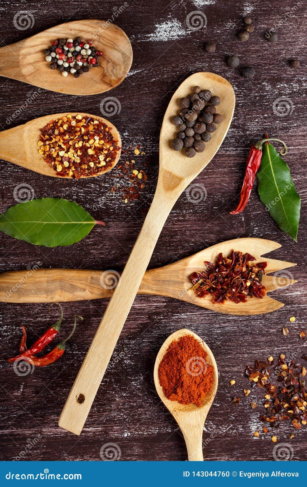 Olika kryddor i tr?skedar p? bakgrund f?r m?rk brunt Olika typer av paprika och pepparkornet