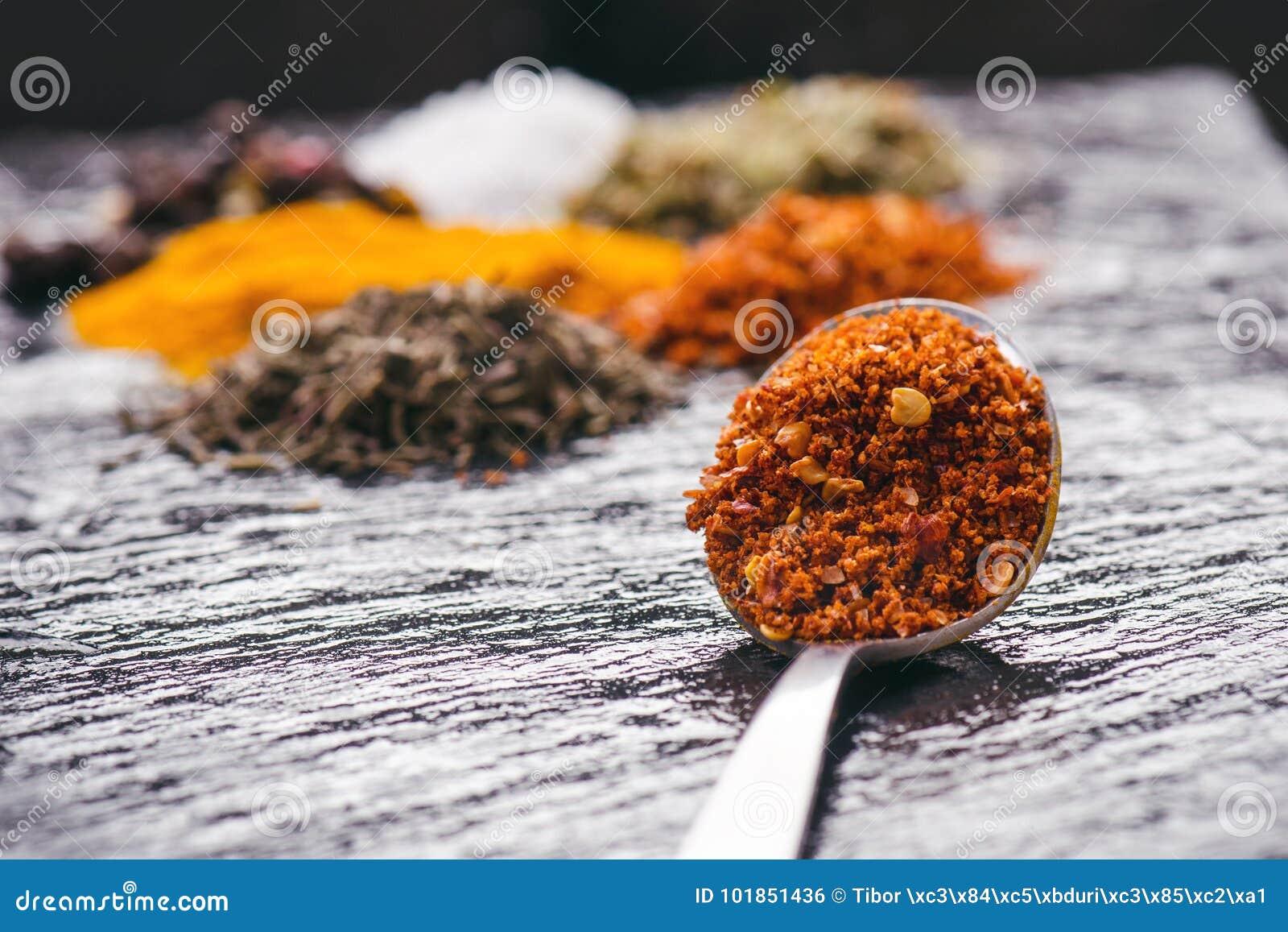 Olika kryddor och örter på en svart kritiserar Järnsked med chilipeppar indiska kryddor Ingredienser för matlagning äta som är su