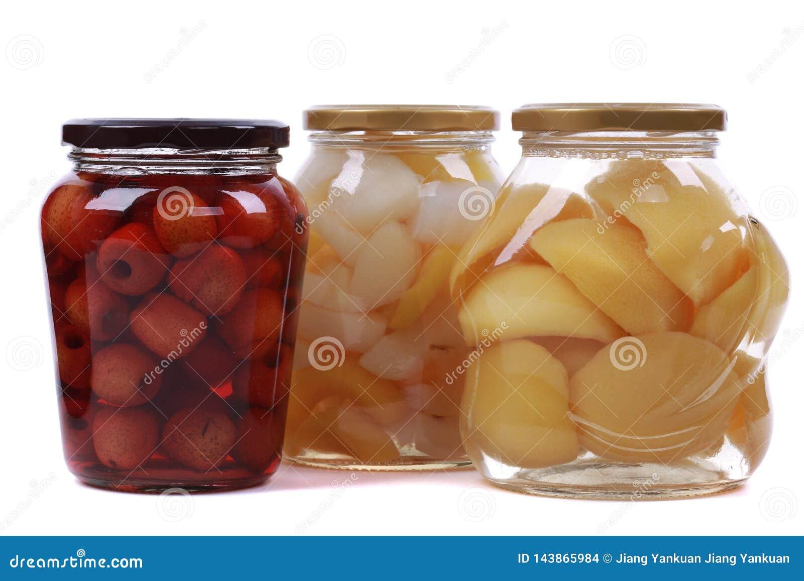 Olika på burk frukter i glasflaskor