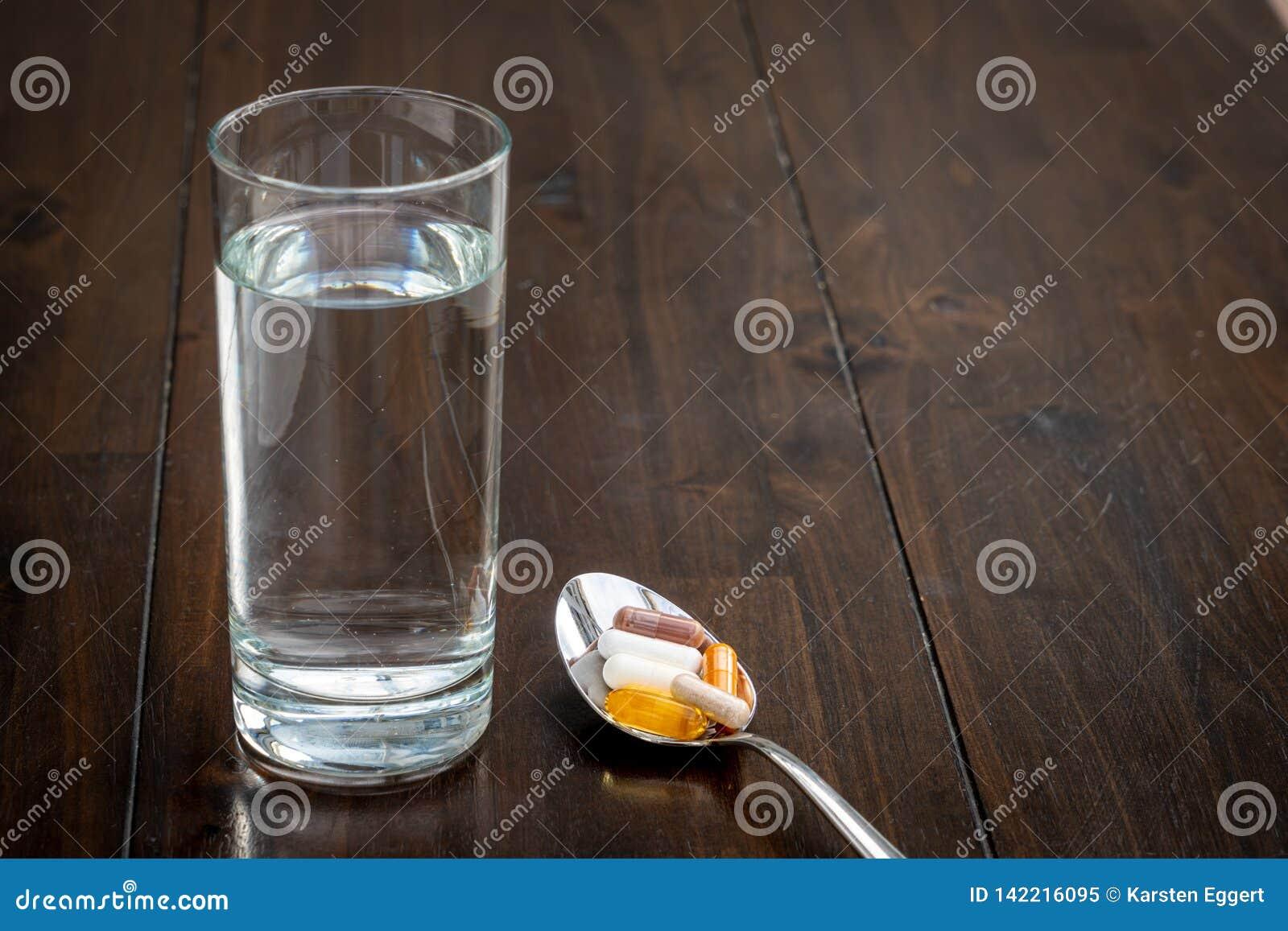 Olika piller är på en sked bredvid ett exponeringsglas av vatten på en brun tabell