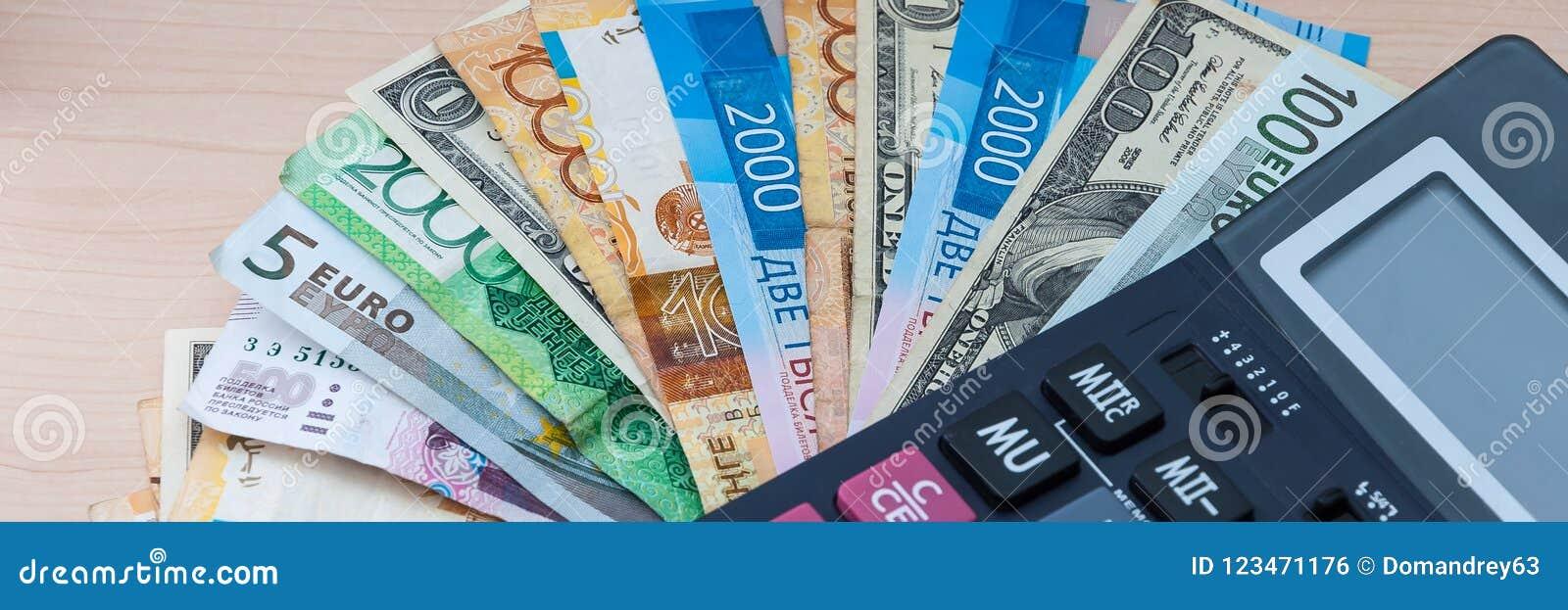 Olika sedlar av olika förtjänster ligger fanen på ditt träskrivbord med en räknemaskin