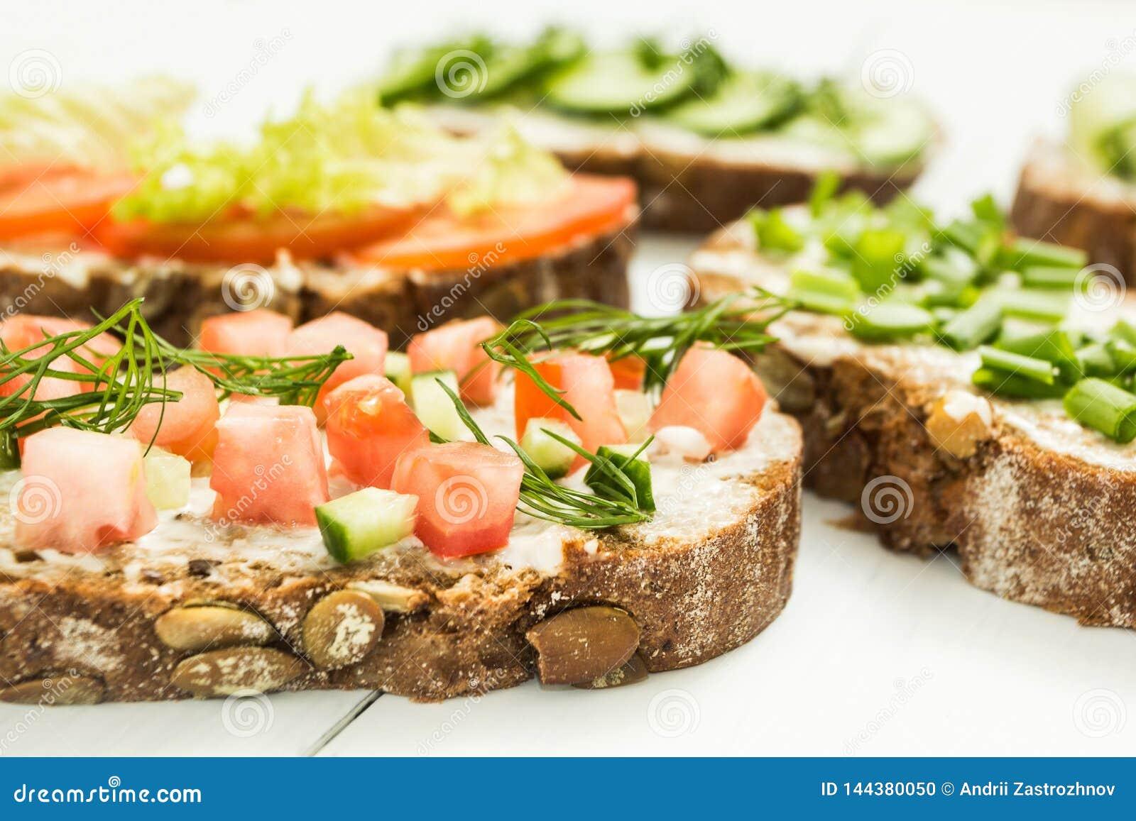 Olika sorter av färgrika smörgåsar på en vit träbakgrund Den sunda livsstilen och bantar