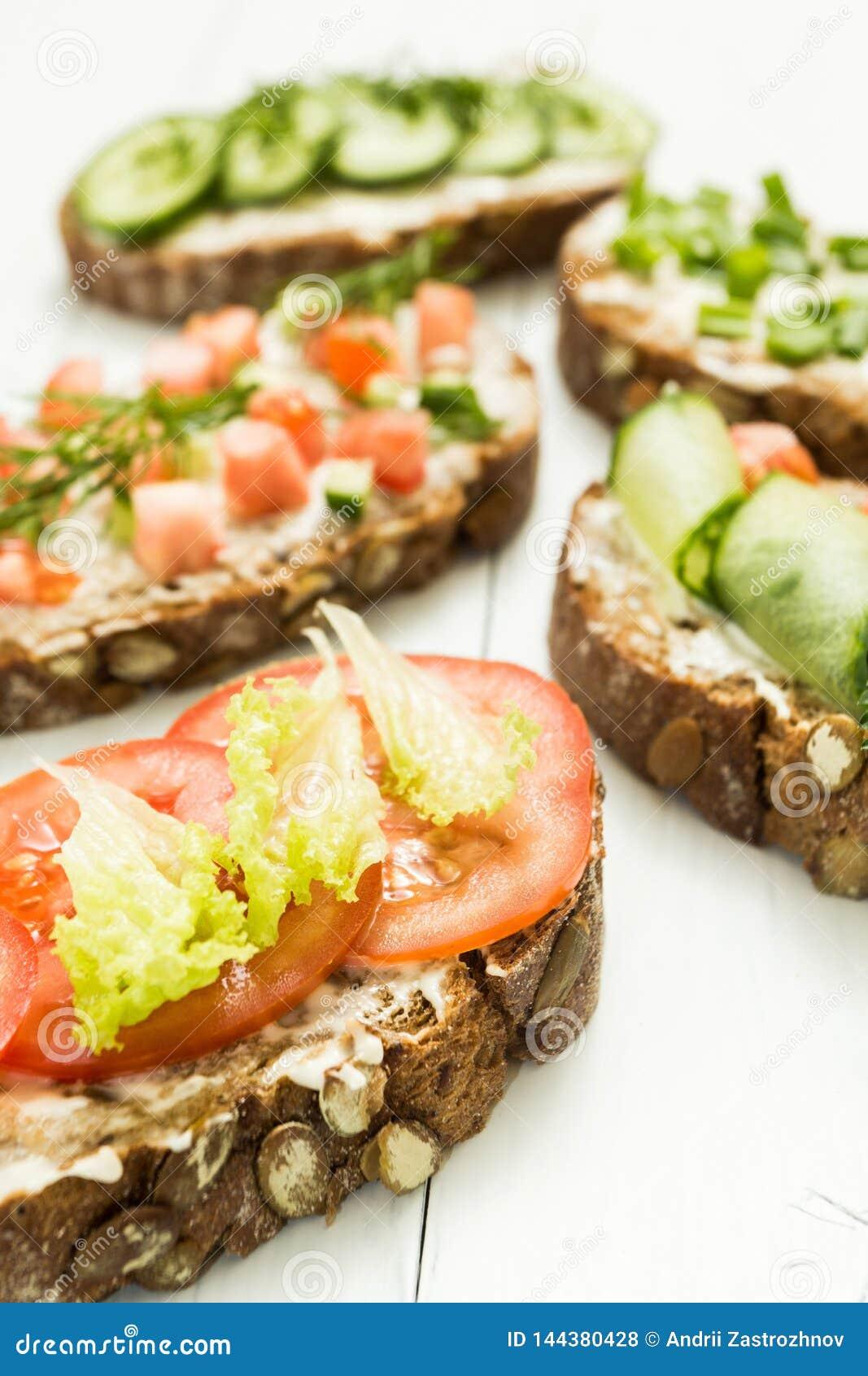 Olika sorter av färgrika smörgåsar på en vit träbakgrund Den sunda livsstilen och bantar vertikalt