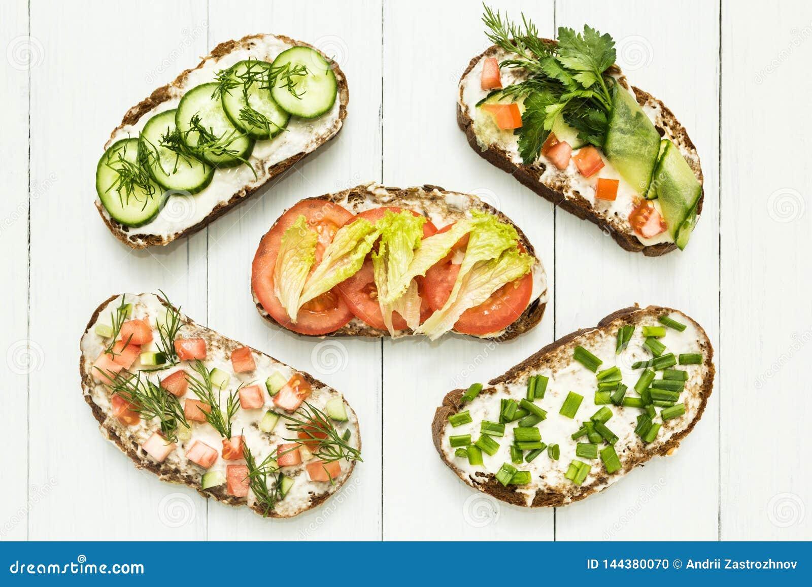 Olika sorter av färgrika smörgåsar på vit träbakgrund från ovannämnd bästa sikt Partistartknapp eller aptitretare - lägenheten lä