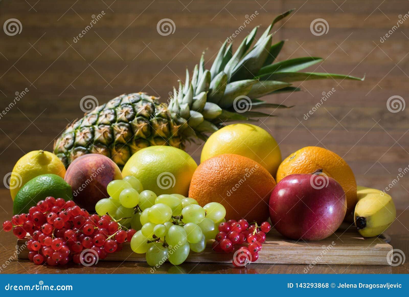 Olika sorter av frukter på träbrädet på tabellen med brun bakgrund