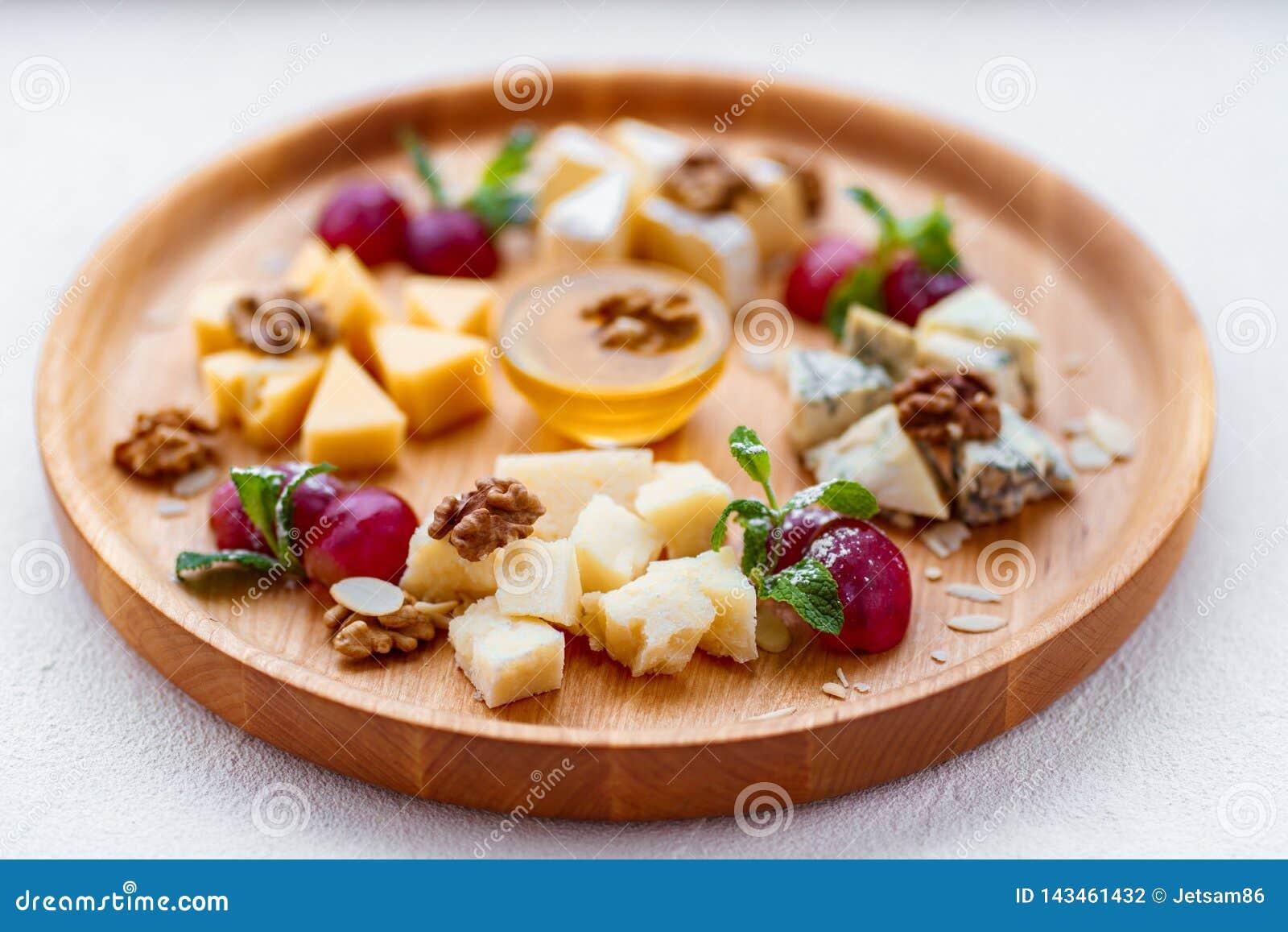 Olika sorter av ostar på träuppläggningsfatet