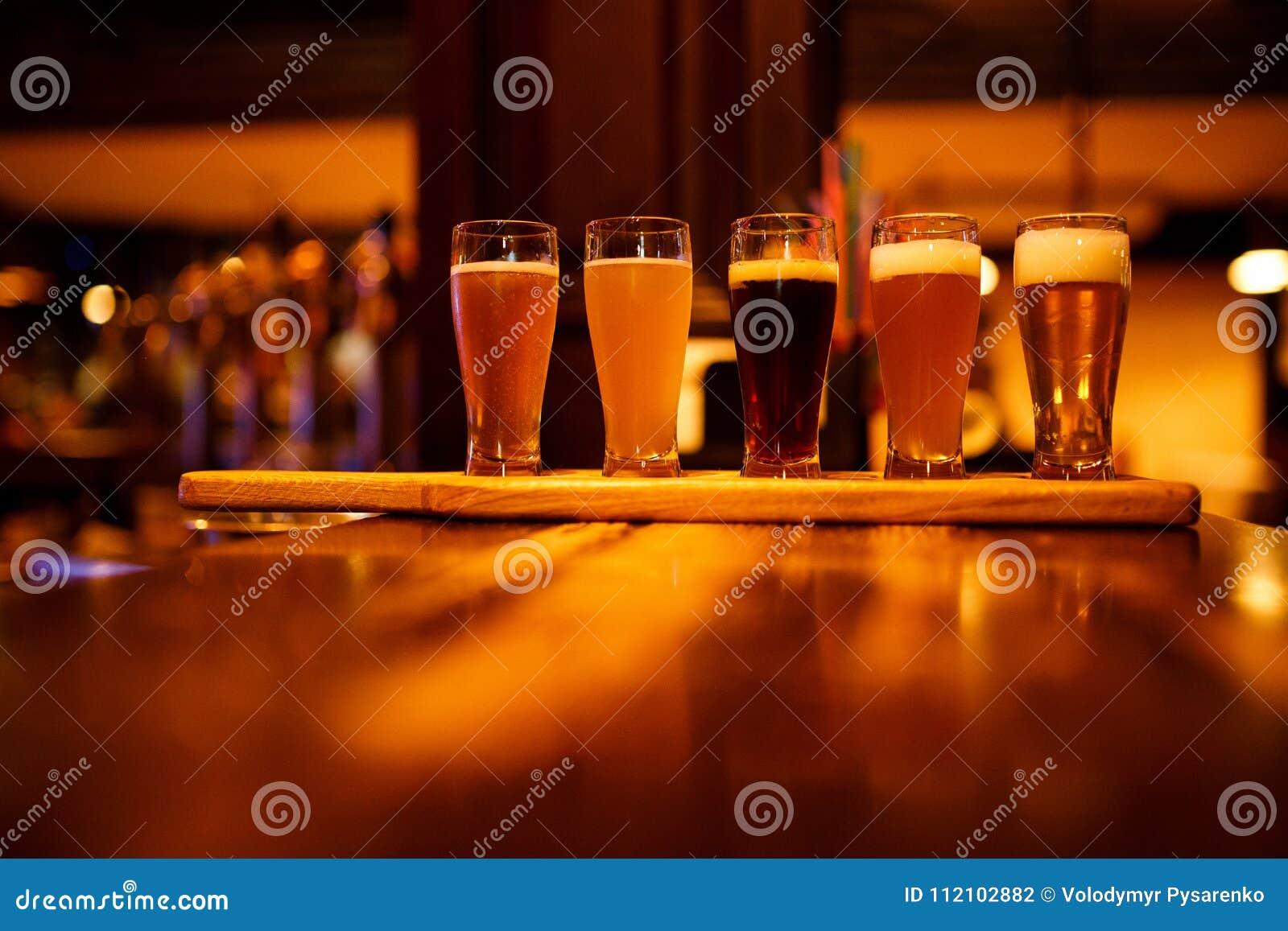 Olika typer av hantverköl i små exponeringsglas på en trätabell i en bar