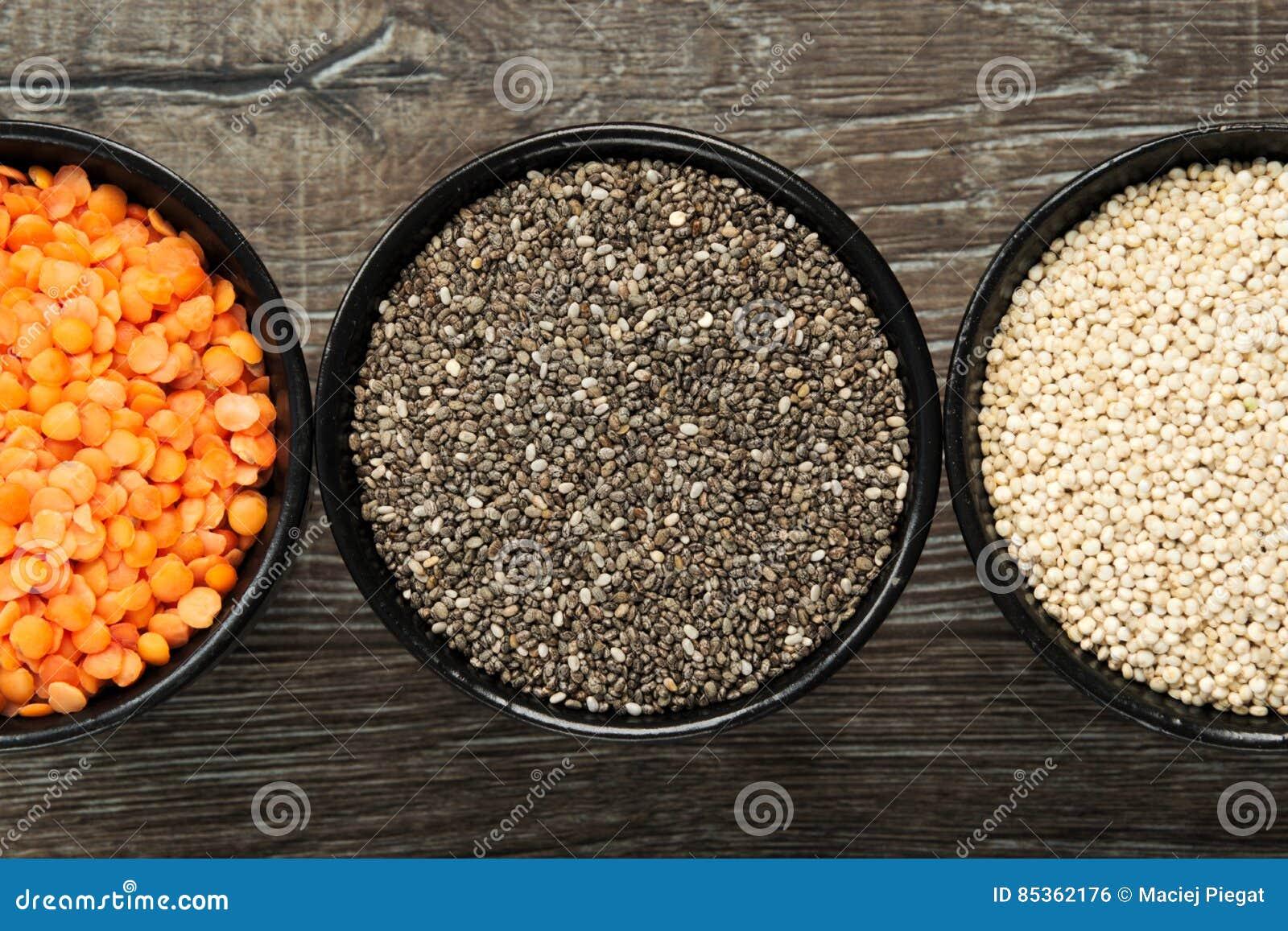 Olika typer av sunda korn i bunkar på träbakgrund