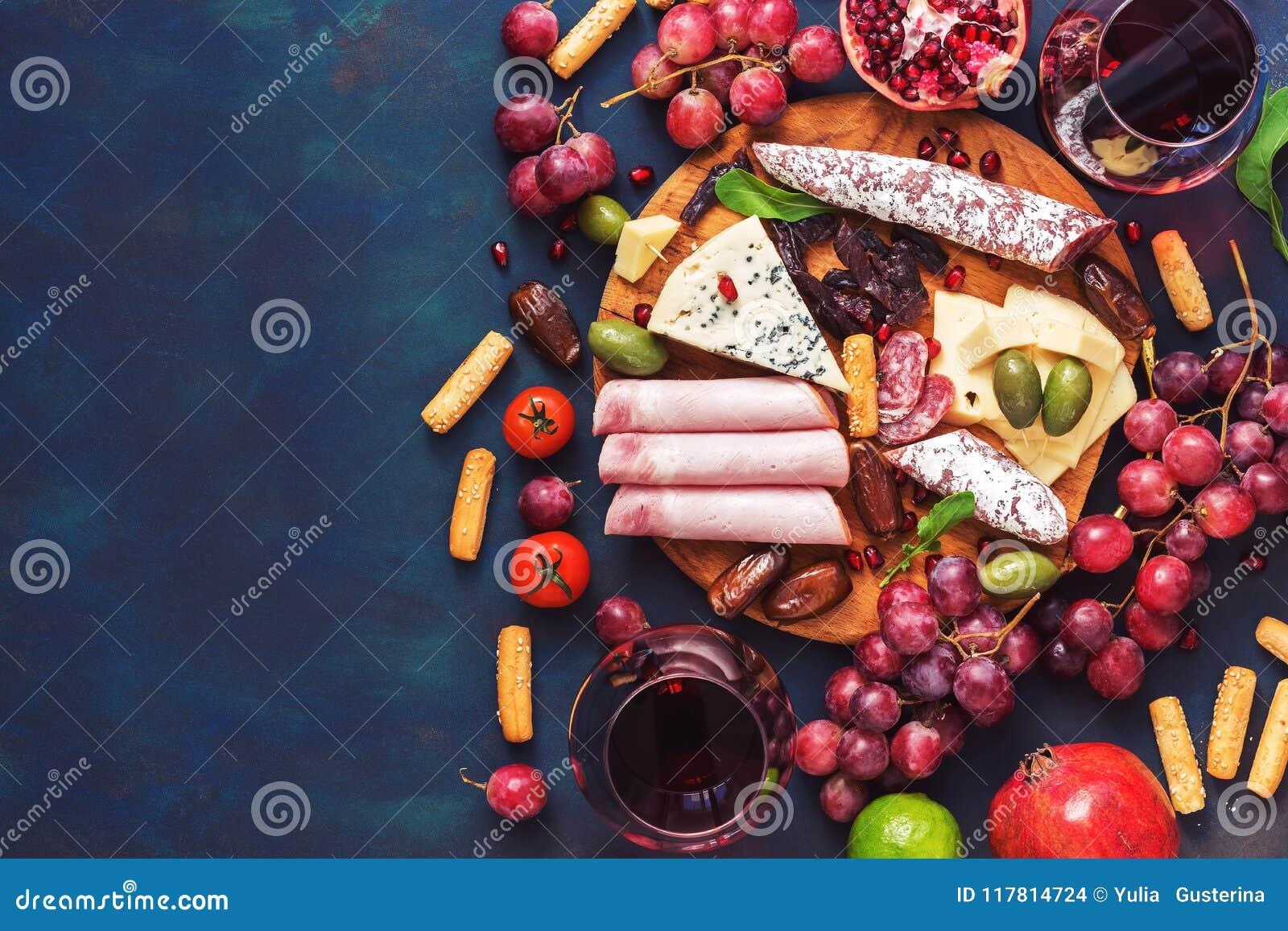 Olikt aptitretare-rött vin, frukter, korvar, ost, grönsaker på en mörk finembakgrund Kopieringsutrymme, bästa sikt