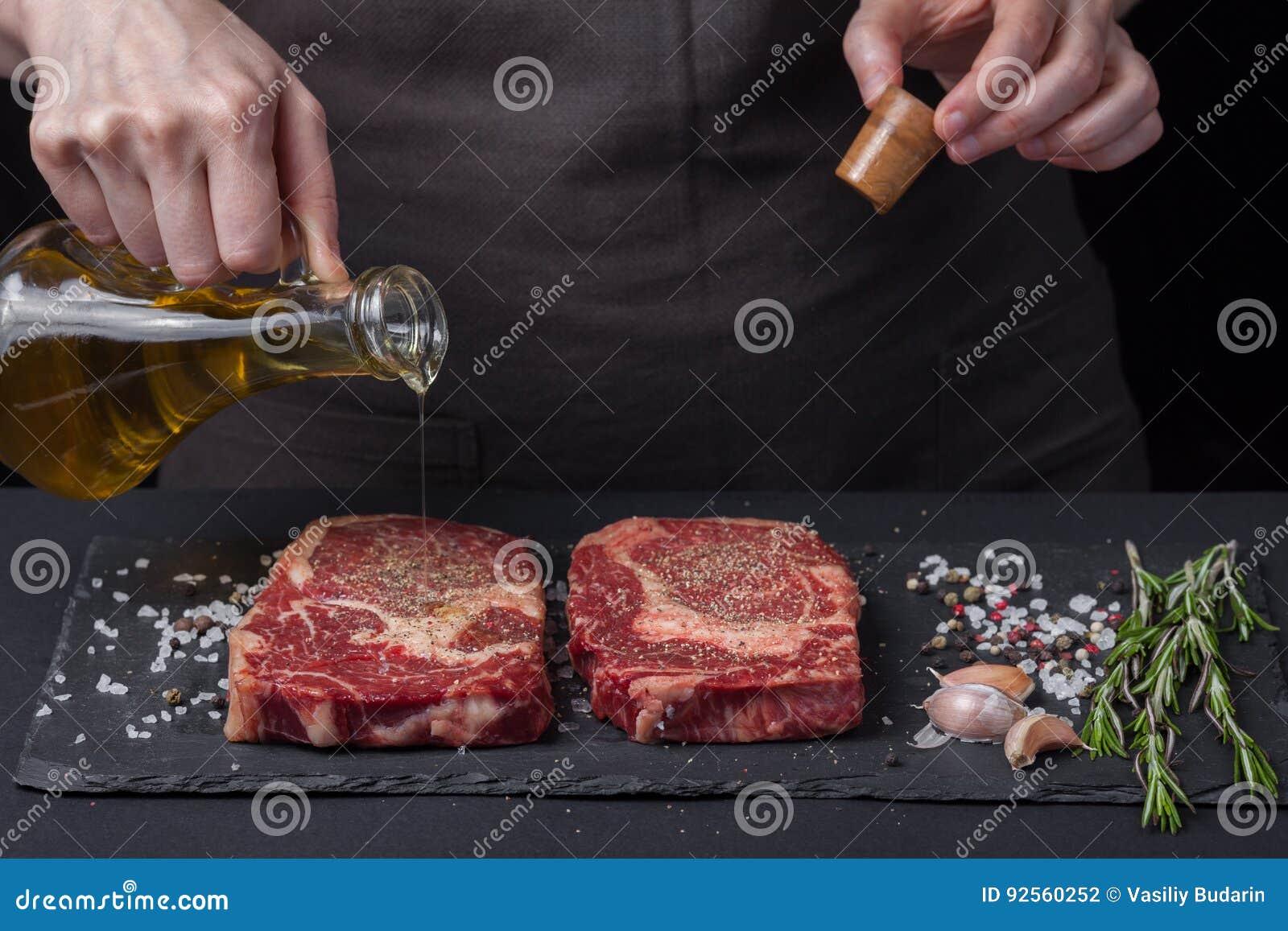 Olio d oliva di versamento del cuoco unico femminile, manzo crudo fresco del ribeye della bistecca due su un fondo scuro Vicino è
