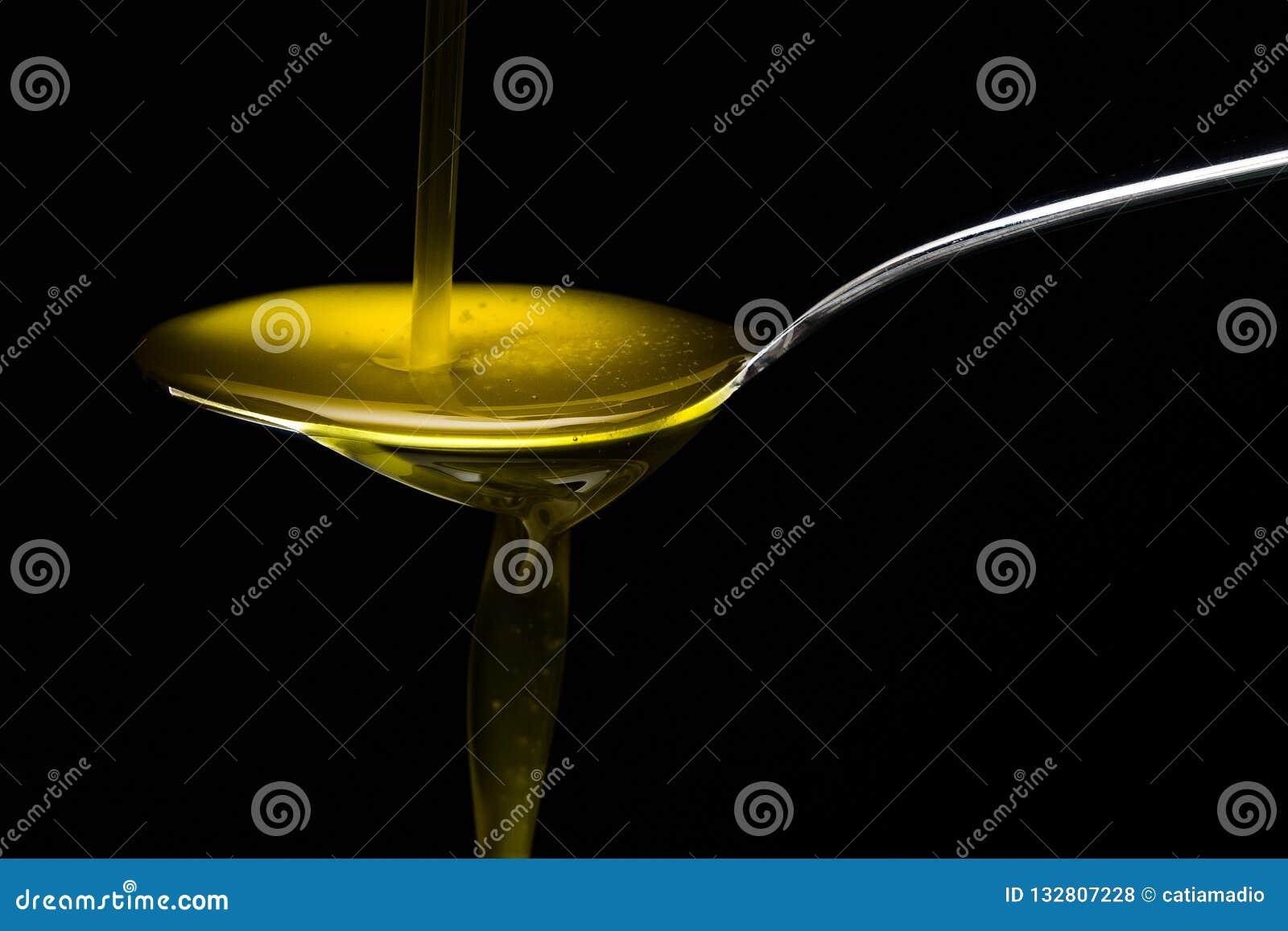 Olio d oliva dorato sopra il cucchiaio del metallo