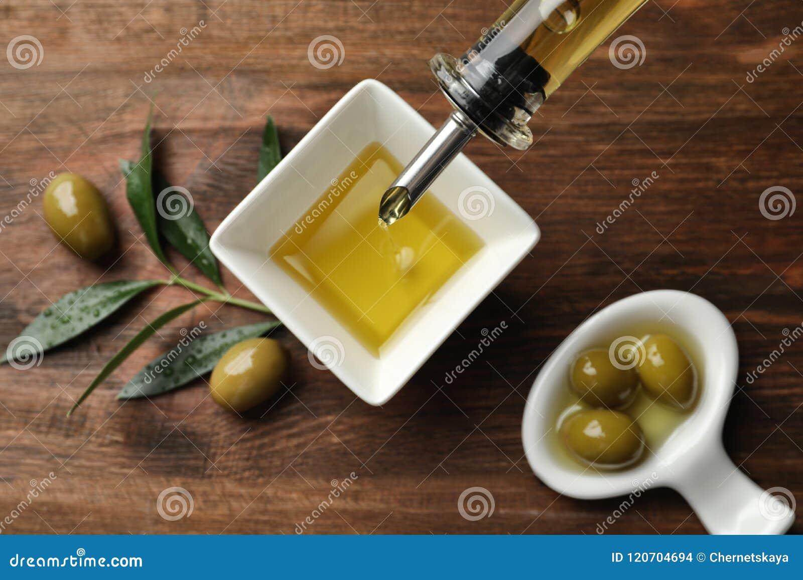 Olio d oliva fresco di versamento nella ciotola sulla tavola,