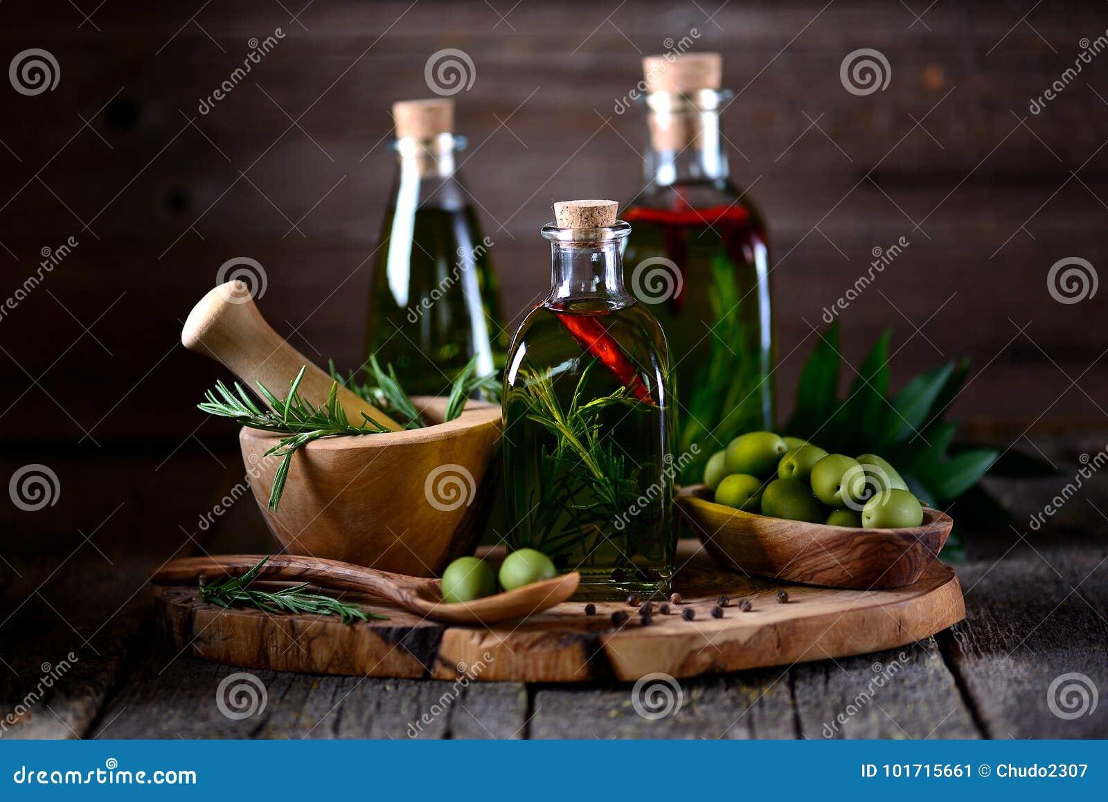 Olio d oliva organico con le spezie e le erbe su un vecchio fondo di legno Alimento sano