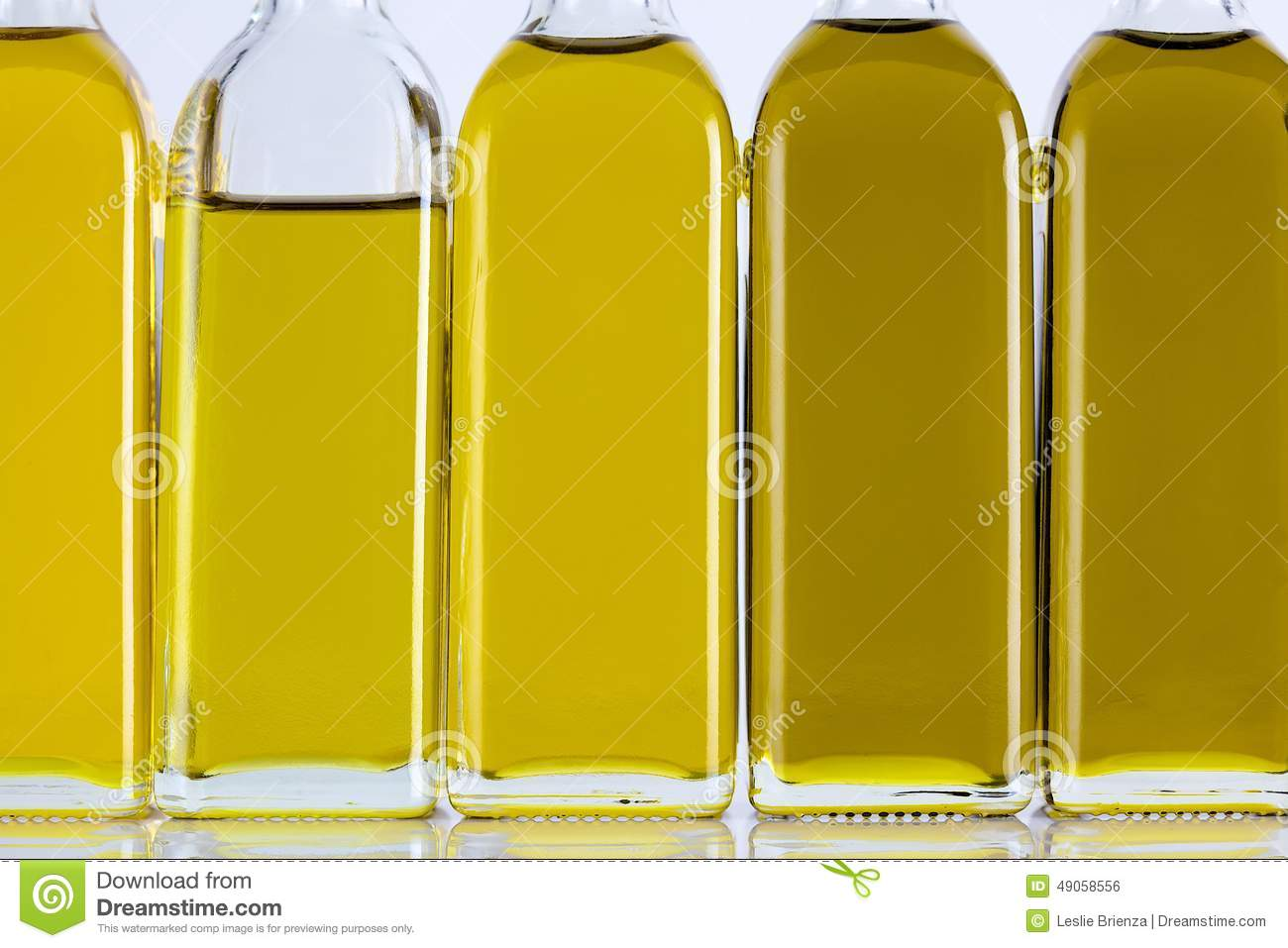 Different Shades Of Yellow olive oil bottles in a row and different shades stock photo