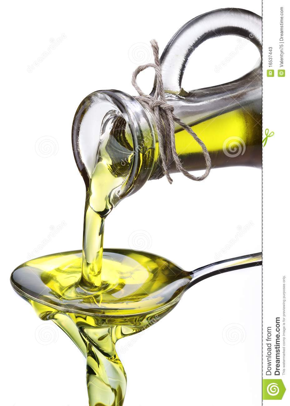 Olive Oil Flowing From Carafe Into The Spoon Stock Photos