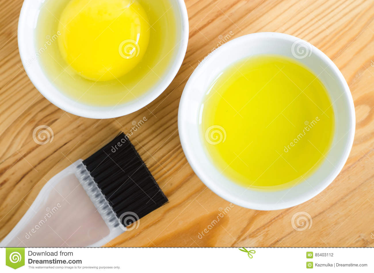 Olive oil and raw egg in a small ceramic bowls for preparing homemade spa face and hair masks. Ingredients for diy cosmetics.