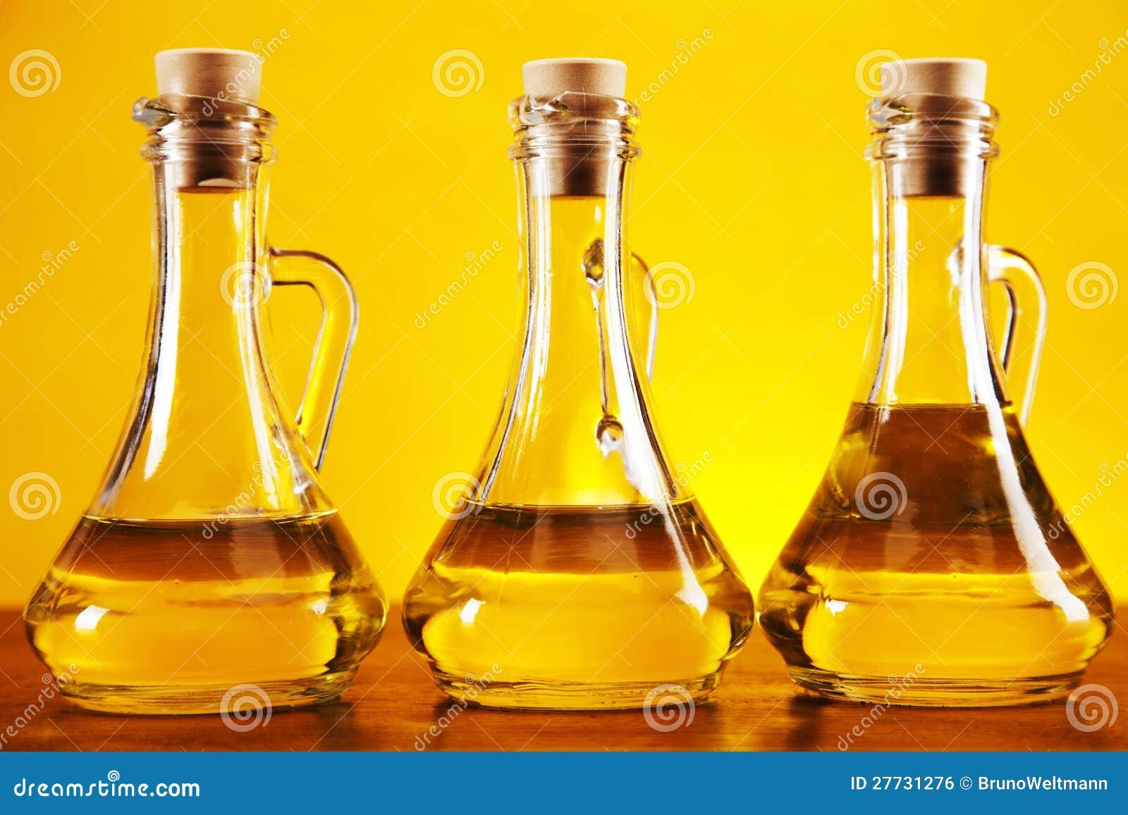 Olivenölflaschen auf gelbem Hintergrund