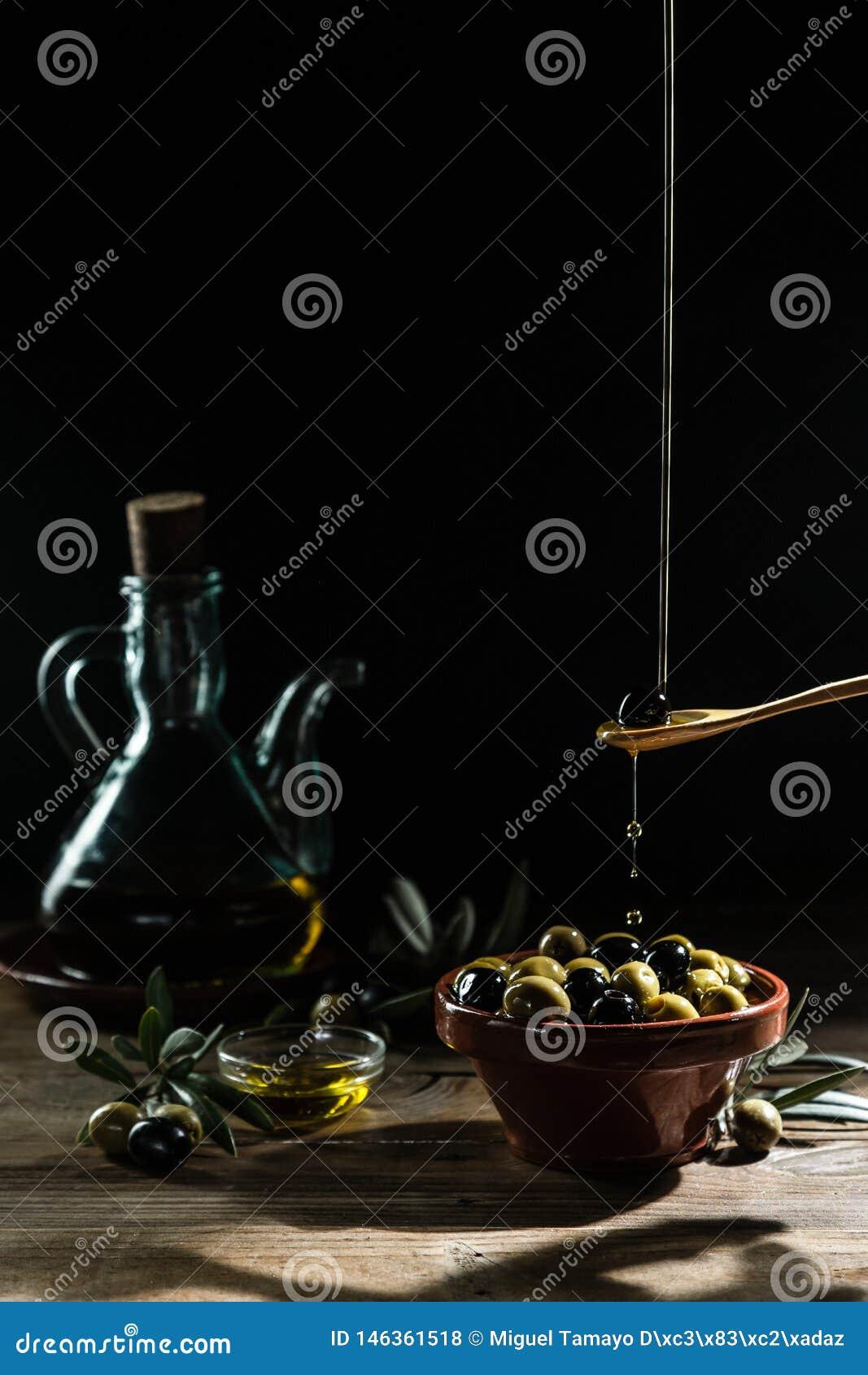 Oliven?l und ?lzweig auf der h?lzernen Tabelle