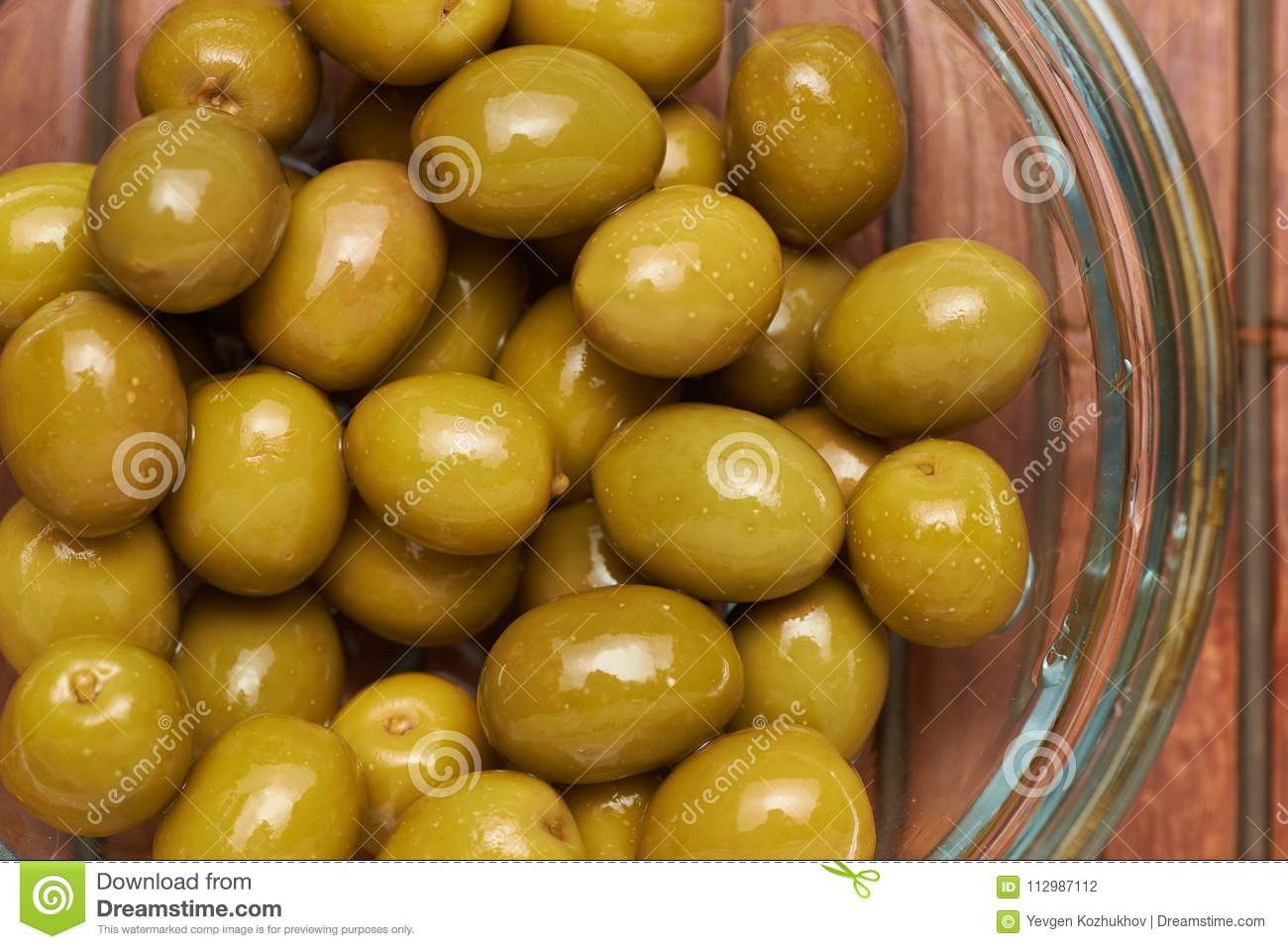 Olives in a glass plate on a brown background