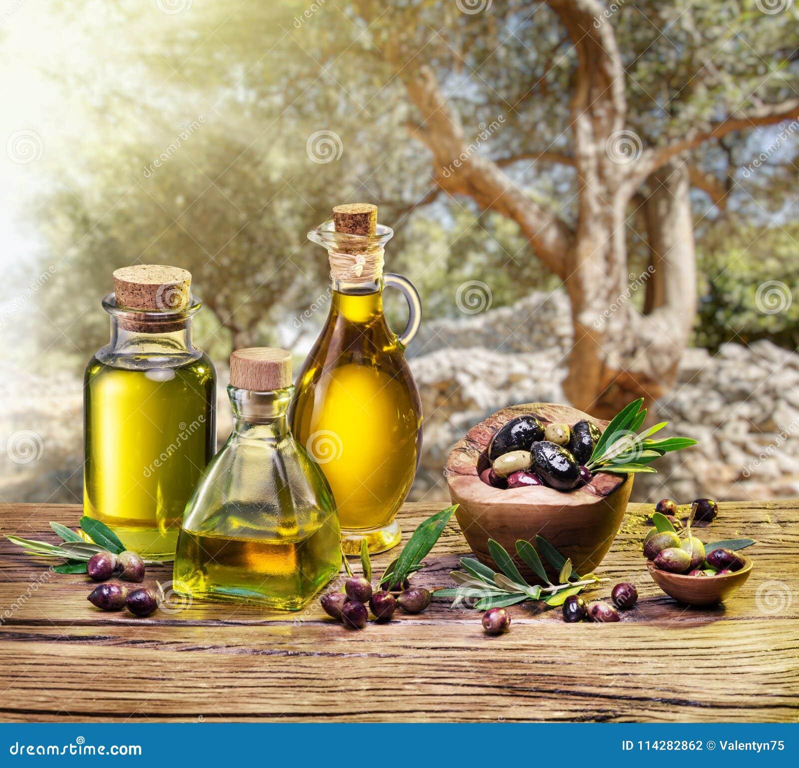 Olivgrüne Beeren in der hölzernen Schüssel und in den Flaschen des Olivenöls auf