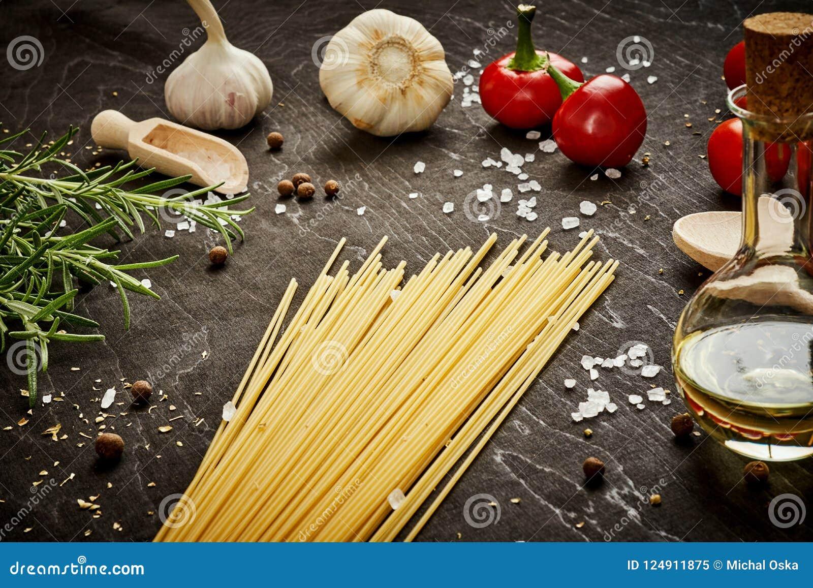 Olivgrüne Pfeffer und Teigwaren des Tomatenknoblauchsalzes auf einer schwarzen Tabelle