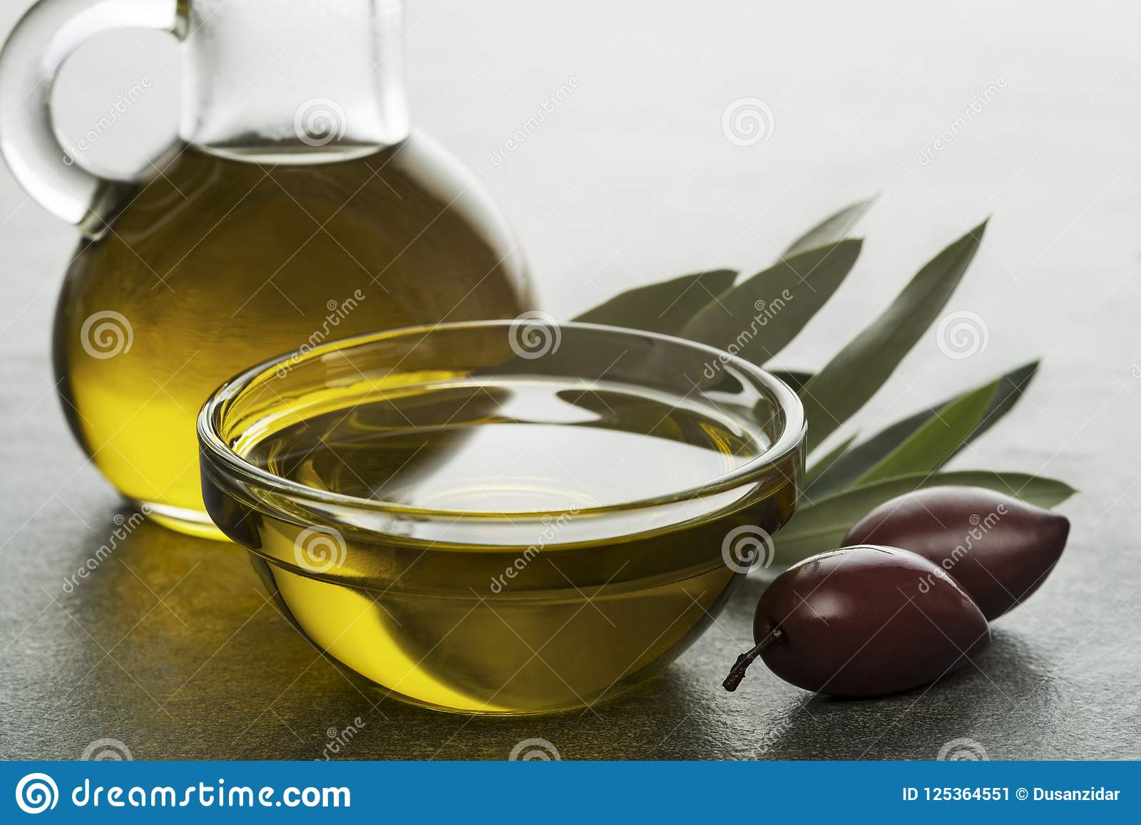 Olivolja i flaska med oliv