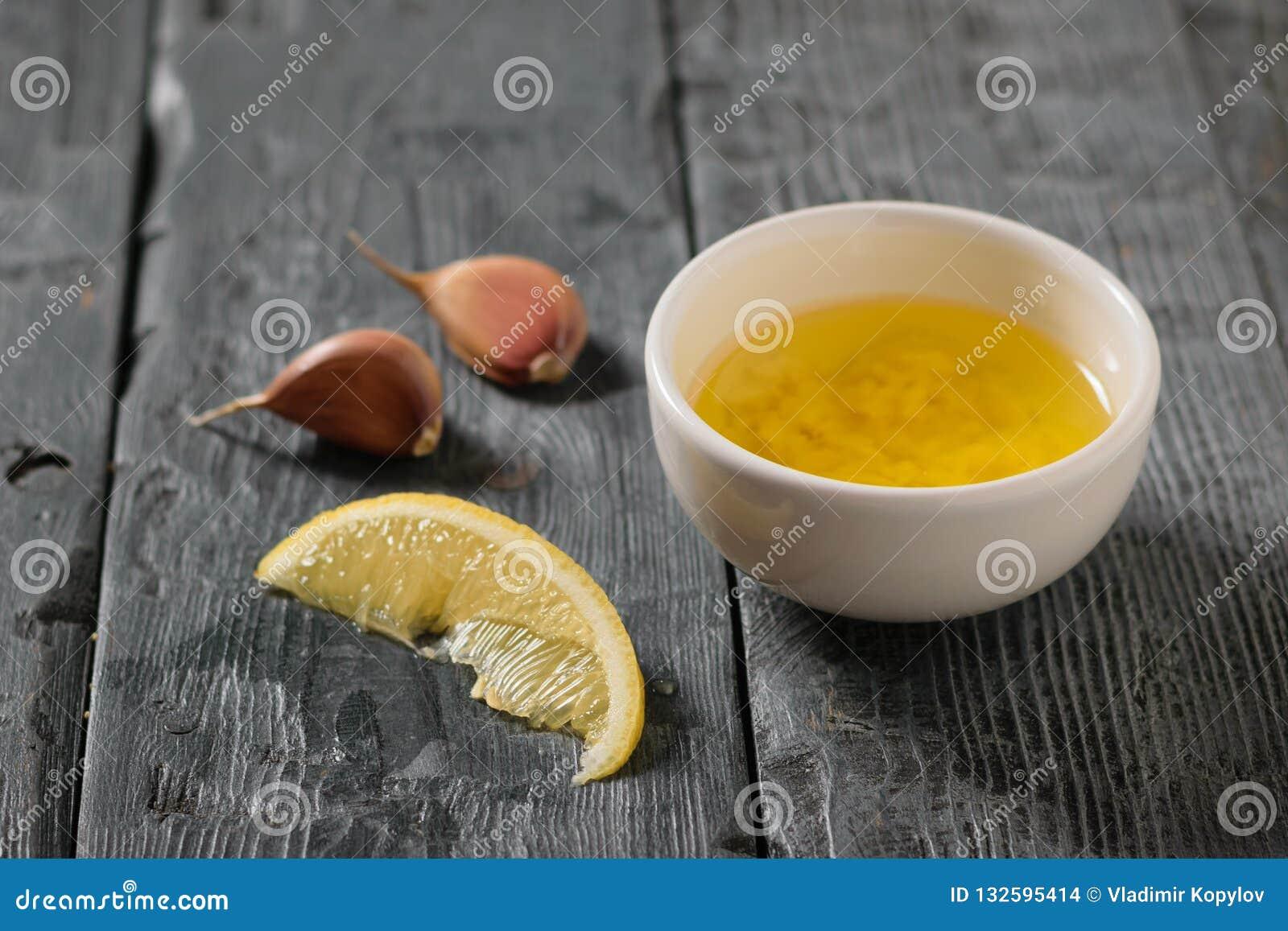 Olivolja med vitlök och citronen i en vit bunke på en mörk tabell Dressingen för bantar sallad