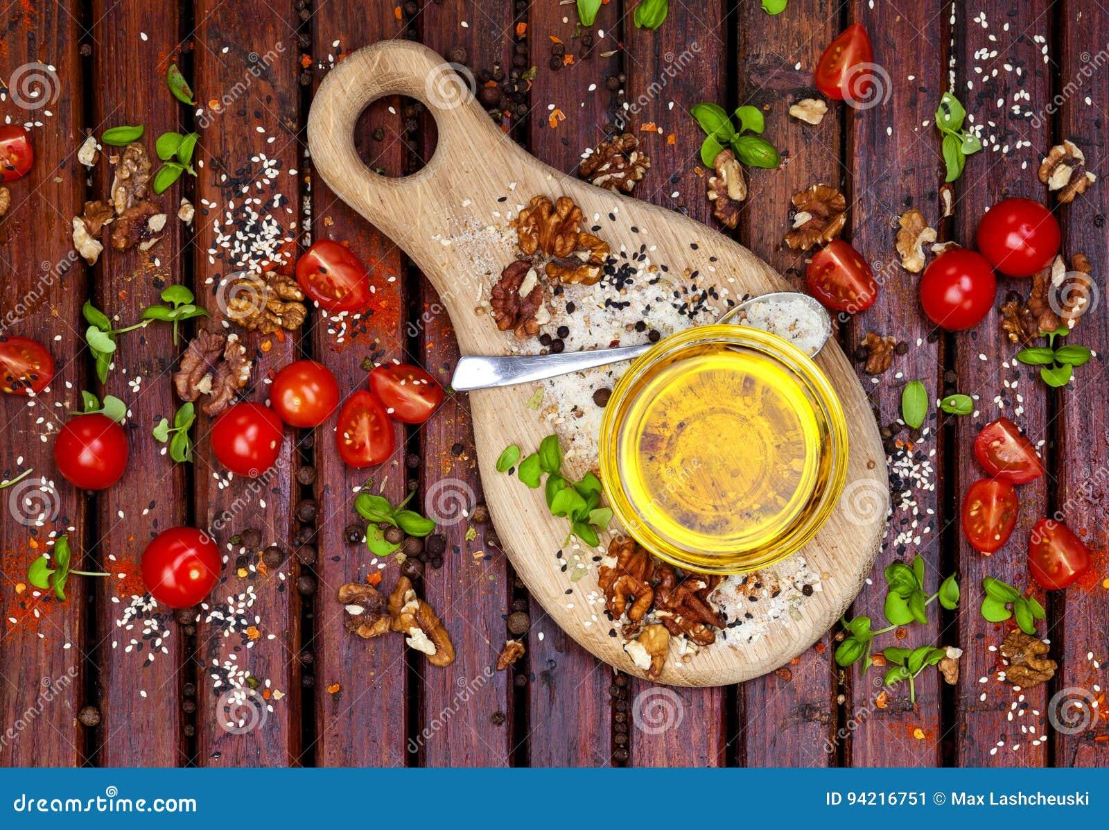 Olja för kryddor, för körsbärsröda tomater, basilika- och grönsakpå den mörka trätabellen, bästa sikt