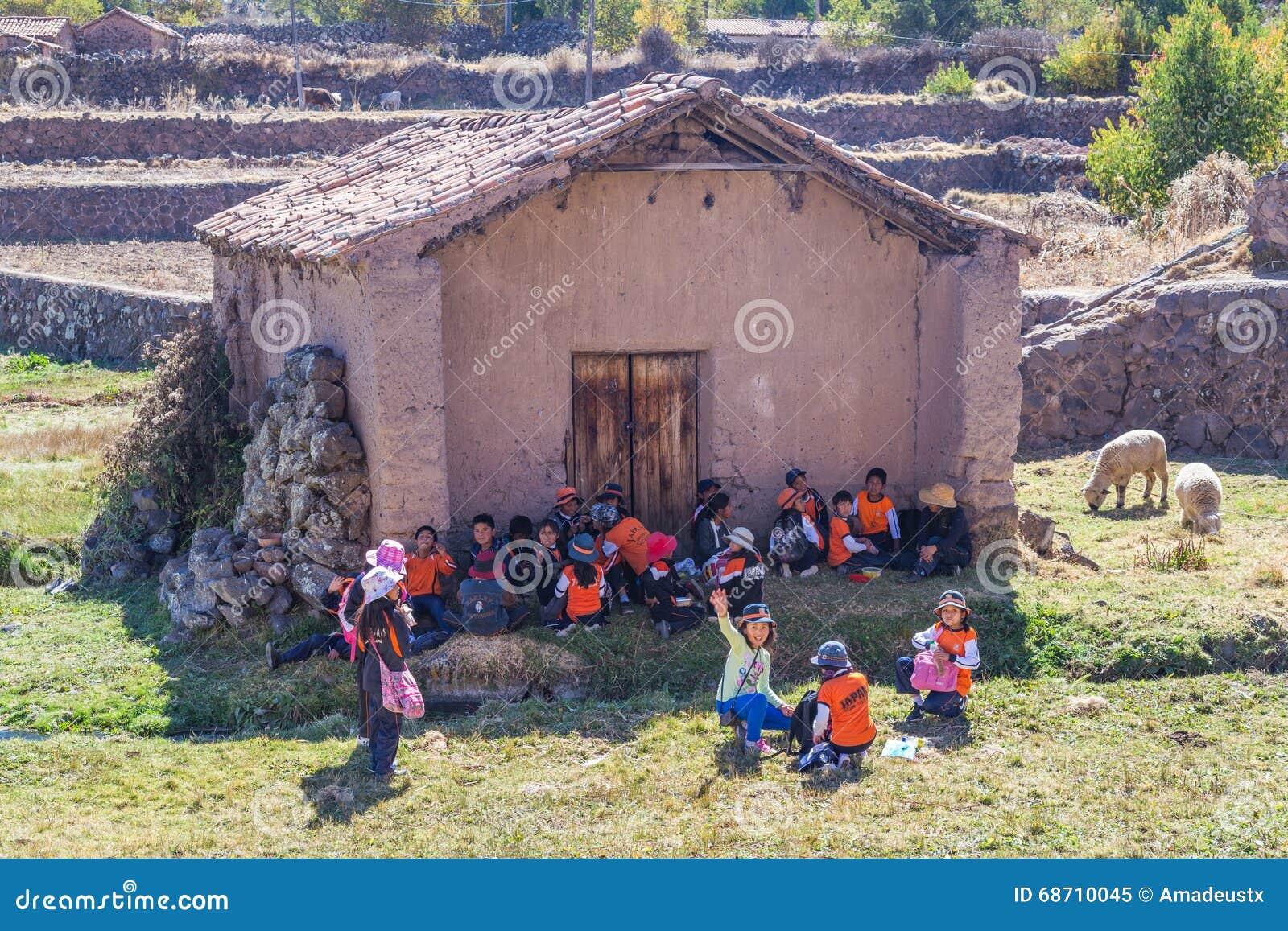 Ollantaytambo, Peru - circa Juni 2015: De kinderen in traditionele Peruviaanse kleren wachten op een schooldbus dichtbij Cusco, P
