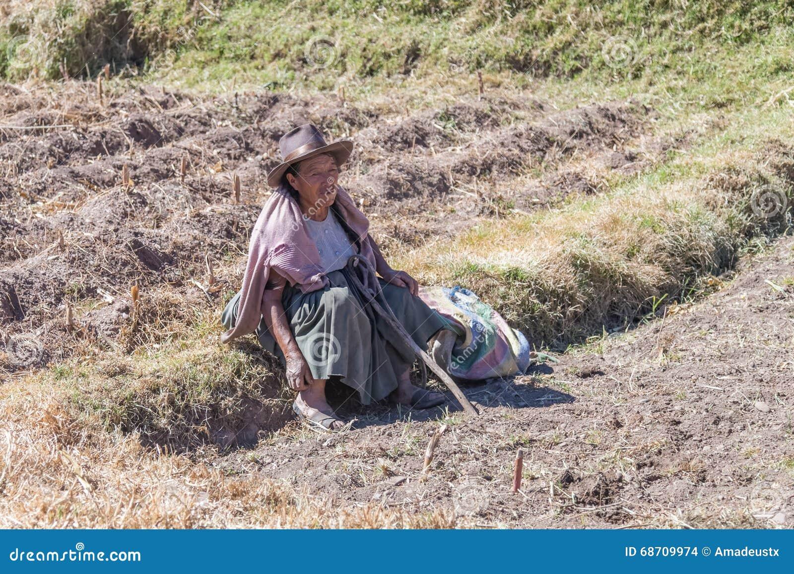 Ollantaytambo, Peru - circa Juni 2015: De oude vrouw in traditionele Peruviaanse kleren zit op het gebied dichtbij Cusco, Peru