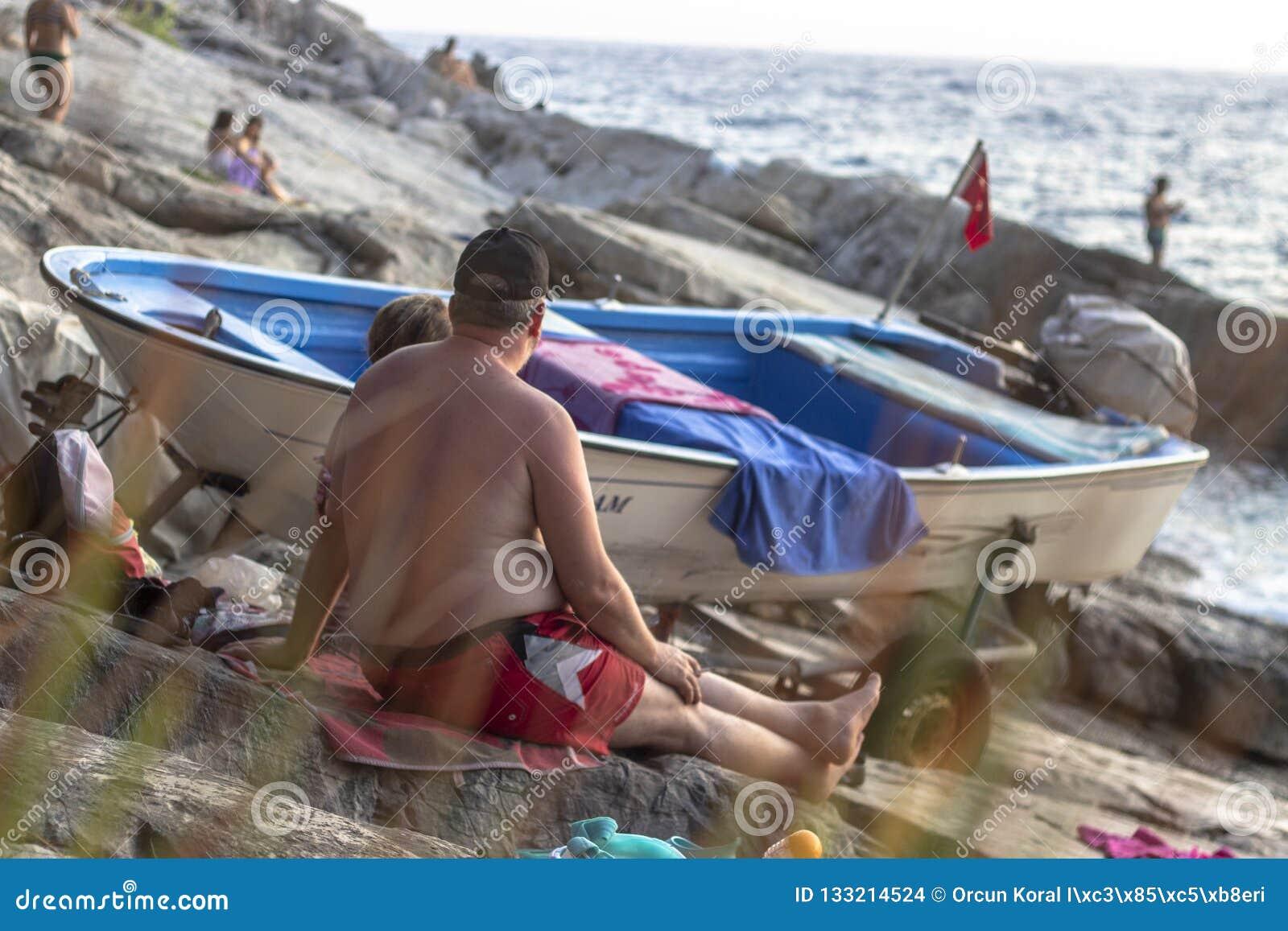 OLUDENIZ - FETHIYE, DIE TÜRKEI - 24. AUGUST 2018 Sauberes Trieb von den Leuten, die auf dem Strand auf der Sonnenuntergangzeit si