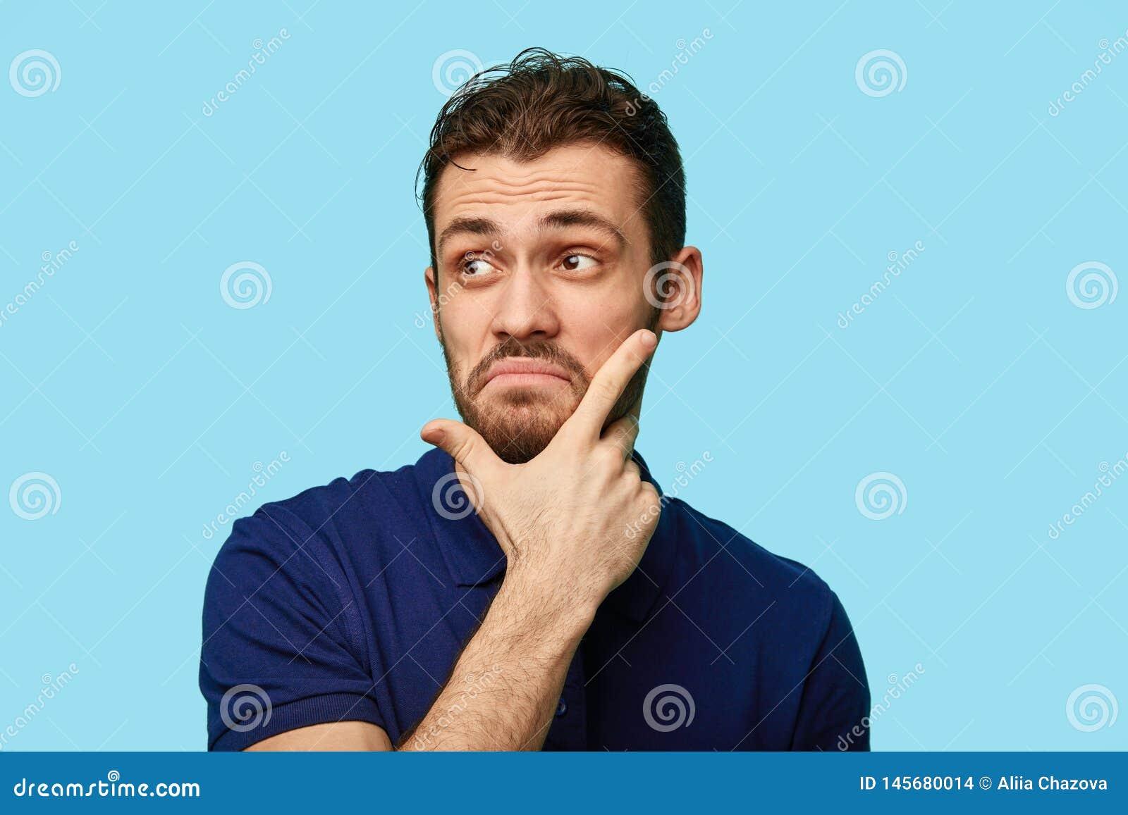 Olycklig frustrerad man som trycker på hans haka