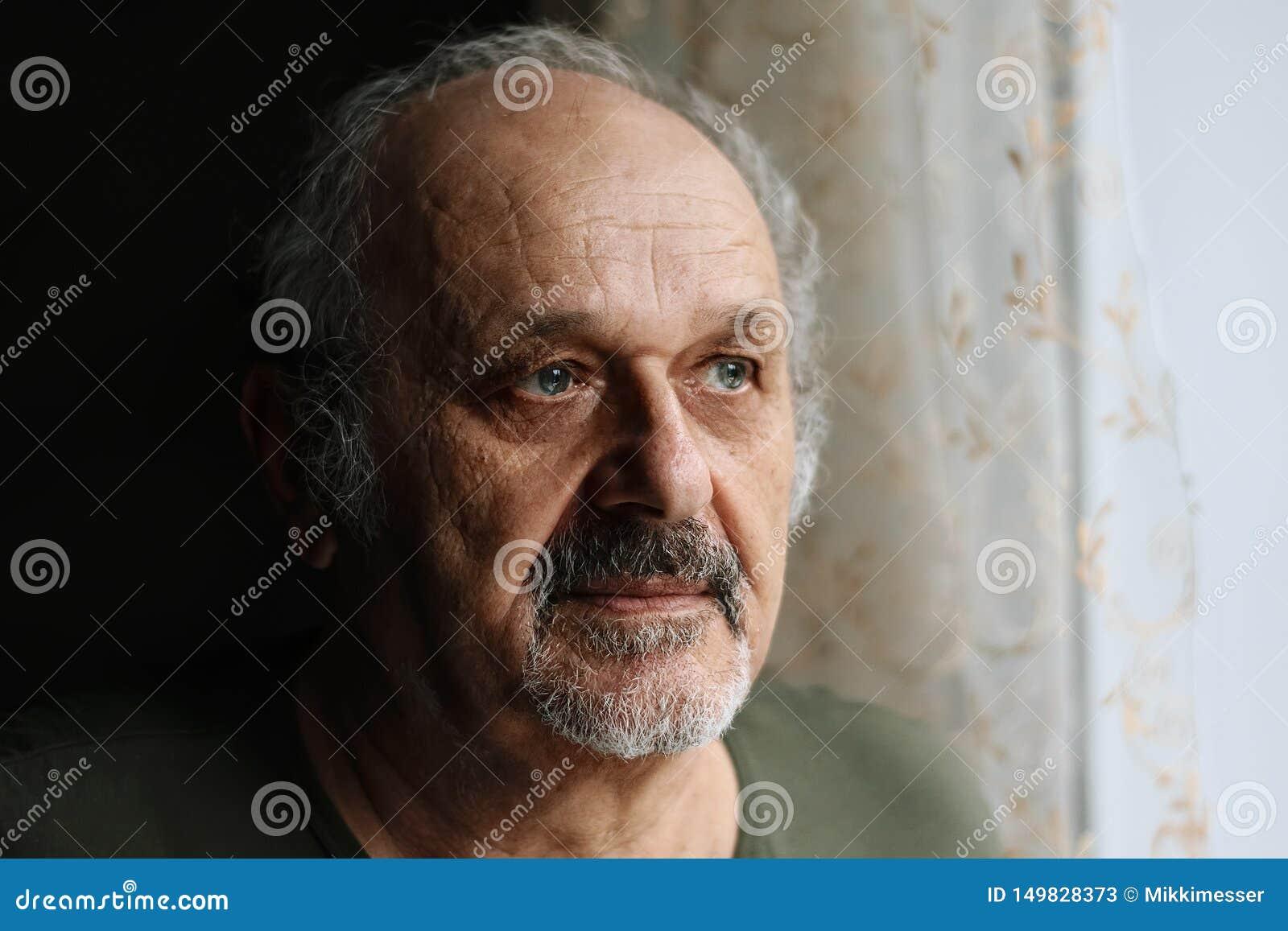 Olycklig gamal man inomhus: hög man med grått skägg- och mustaschanseende nära fönster Ensamhet åldrigt folkproblembegrepp